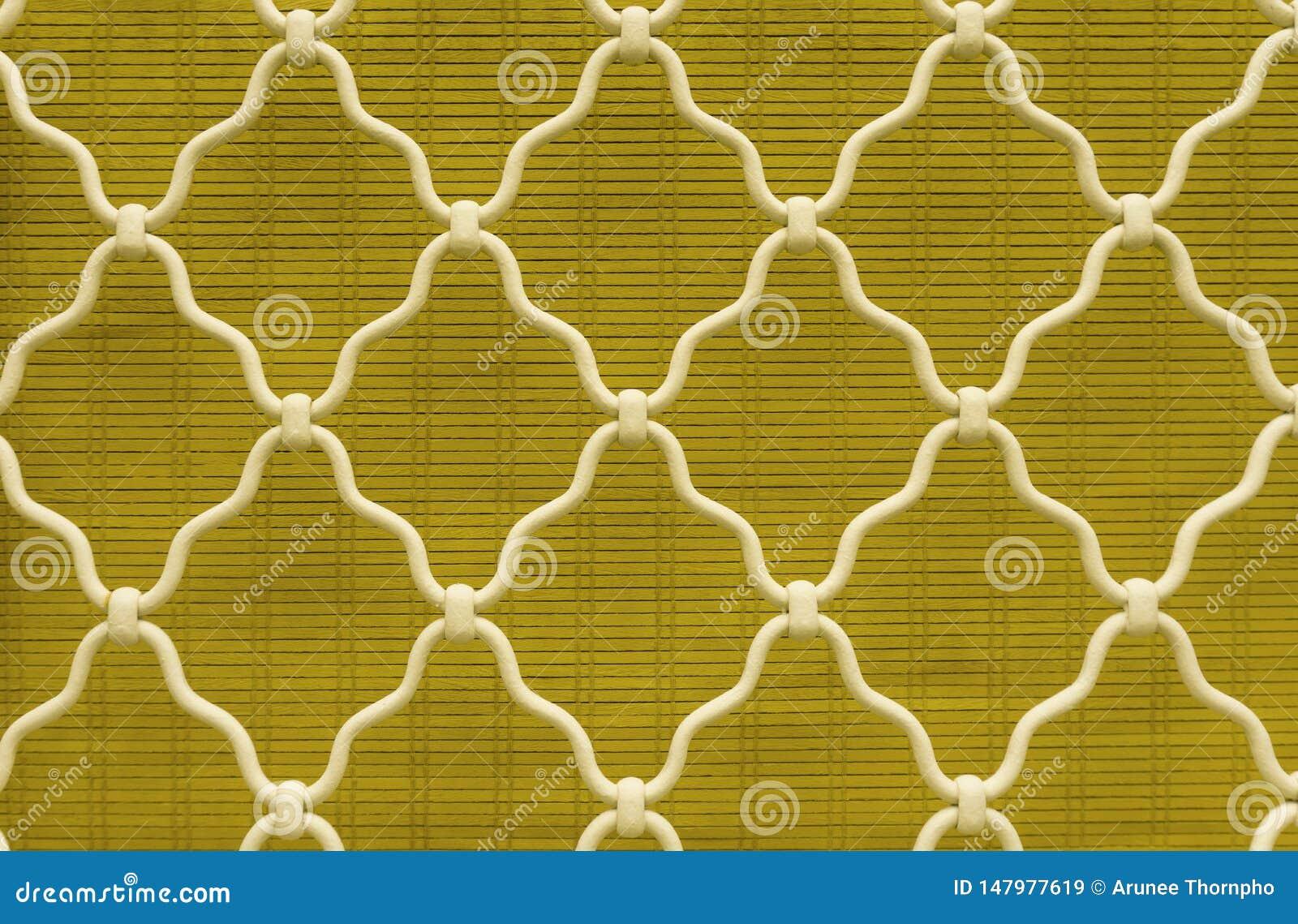 Forma del diamante del acero curvado blanco en la ventana del enrejado, fondo amarillo de cortina de bambú, enrejado del hierro l