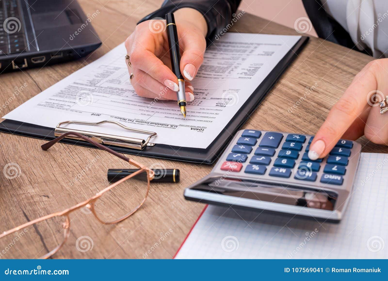Forma di imposta sul reddito delle persone fisiche della limatura della donna 1040, con il calcolatore
