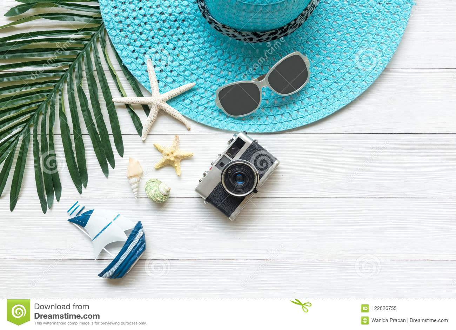 Forma do verão, câmera, estrela do mar, sunblock, vidros de sol, chapéu Curso e férias no feriado, fundo branco de madeira
