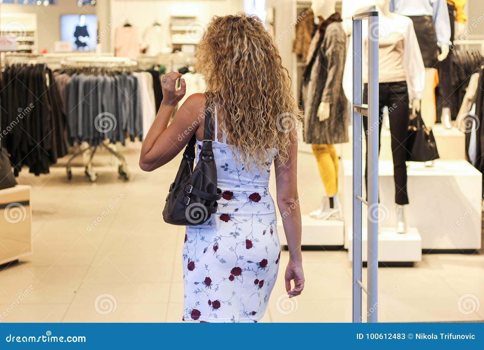 Forma entrando da menina loura encaracolado atrativa e loja de roupa