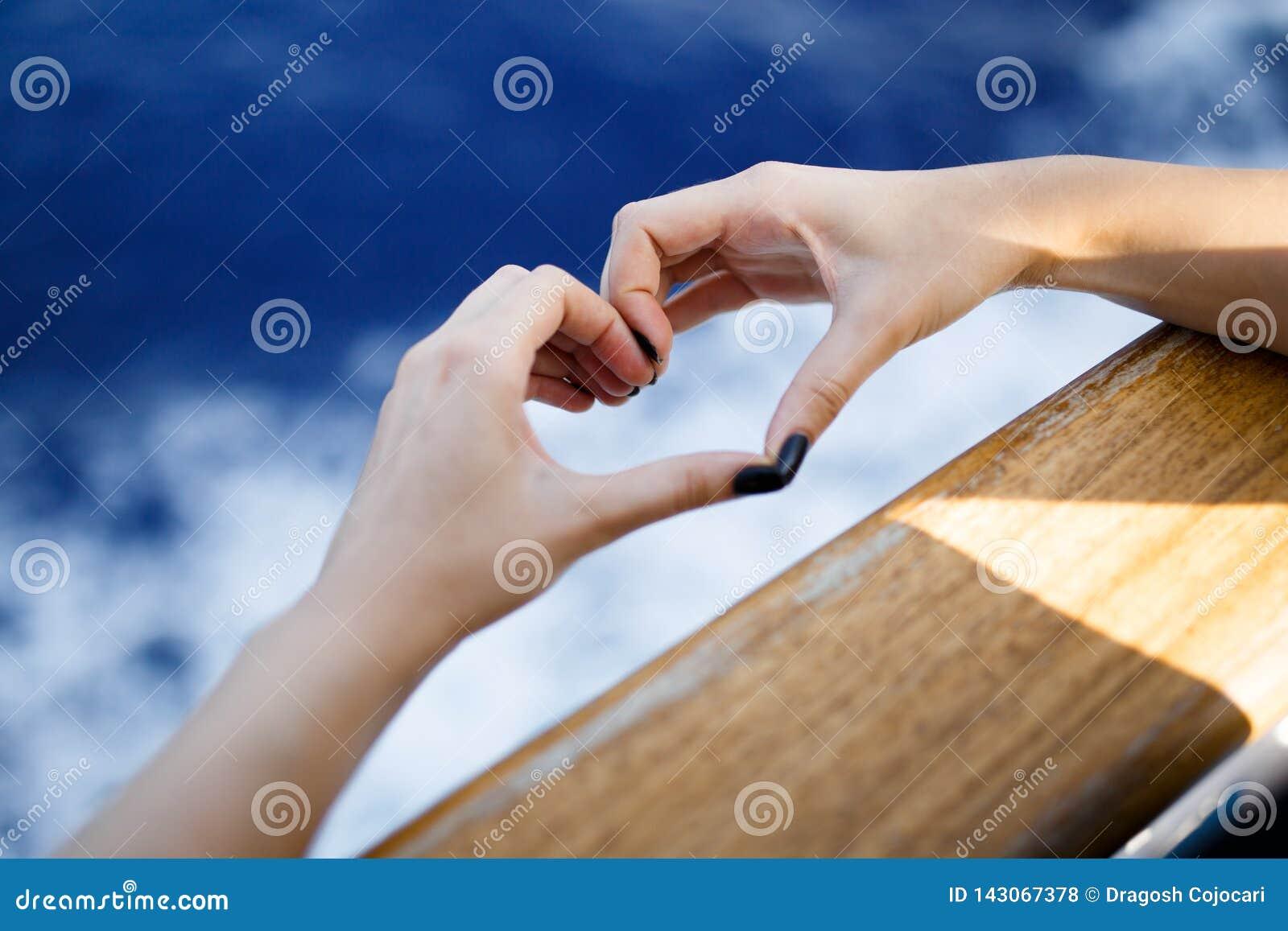 Forma fêmea do coração das mãos que guarda após a placa de madeira Onda da luz solar do bokeh da natureza e fundo azul das ondas