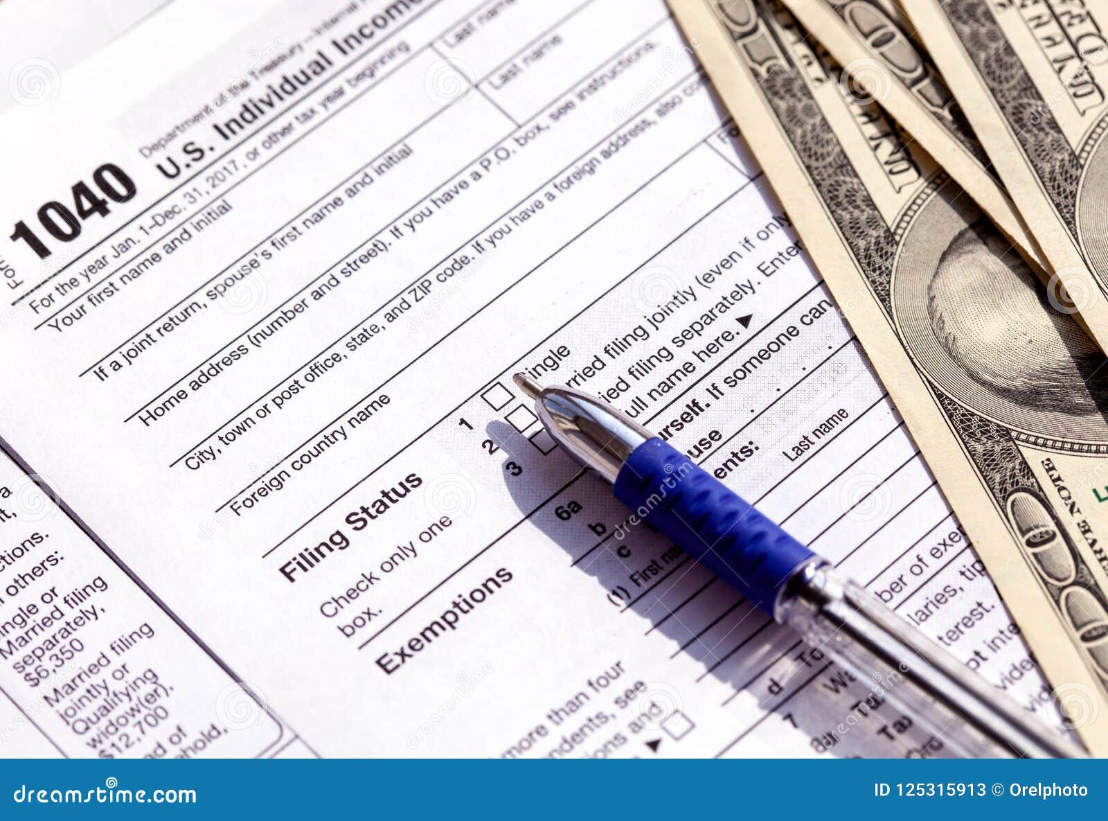 Forma, penna e banconote in dollari di imposta degli Stati Uniti 1040 Concetto del rimborso di imposta
