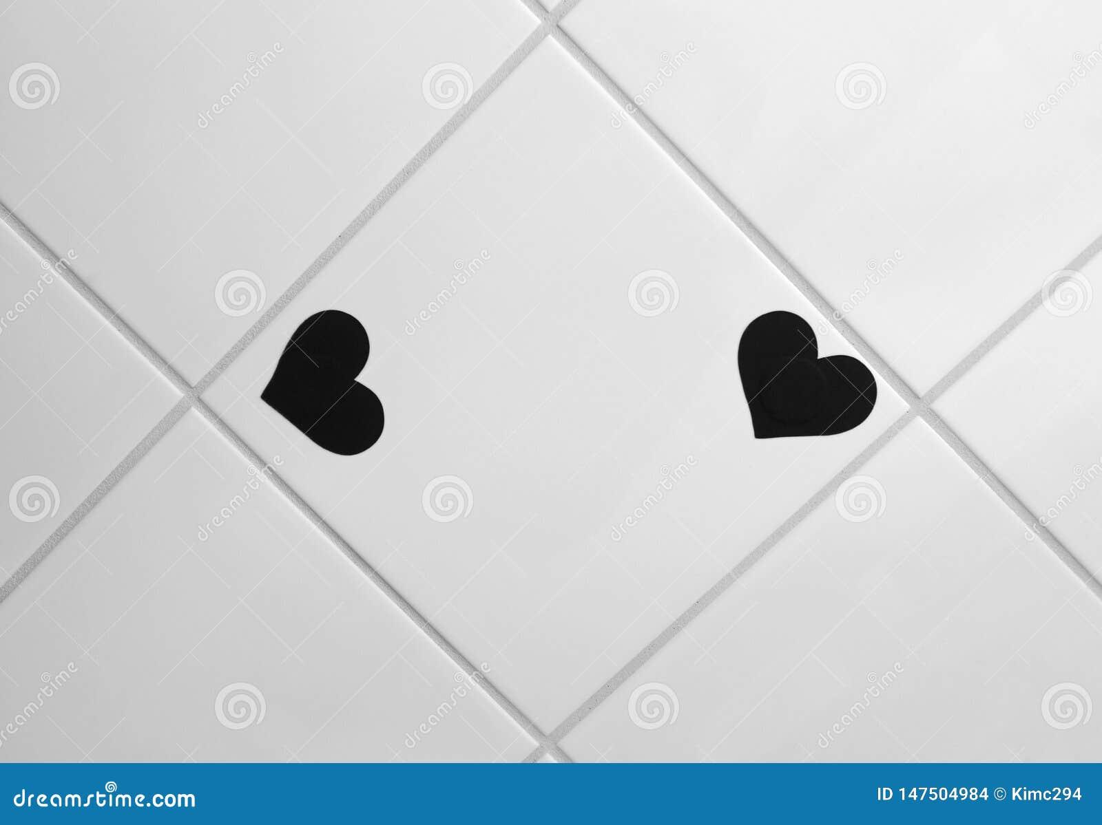 Formade liten svart hjärta två klistermärkear på den glasade tegelplattan