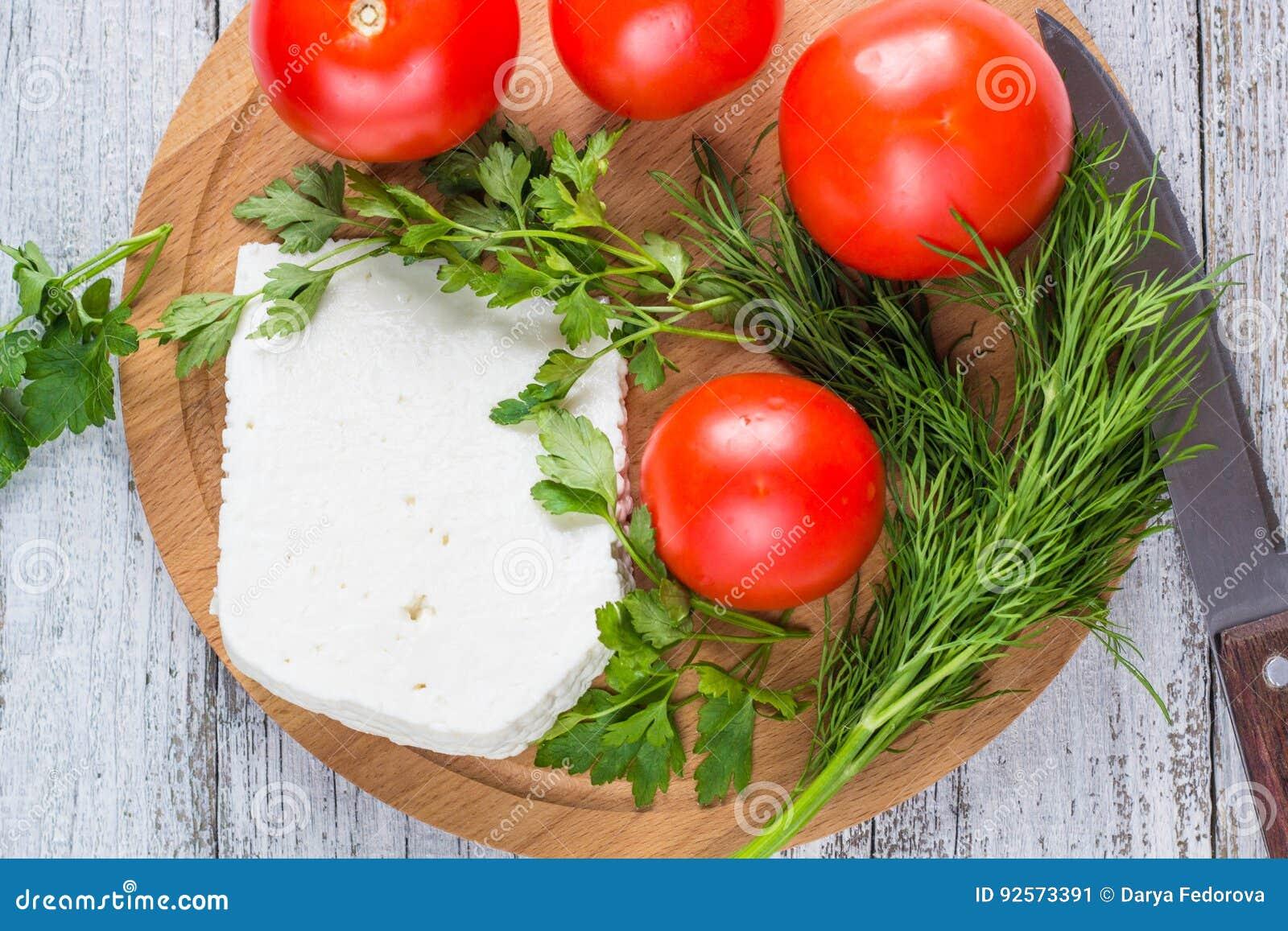 Formaggio bianco, coltello, prezzemolo, pomodori su un fondo dei bordi di legno