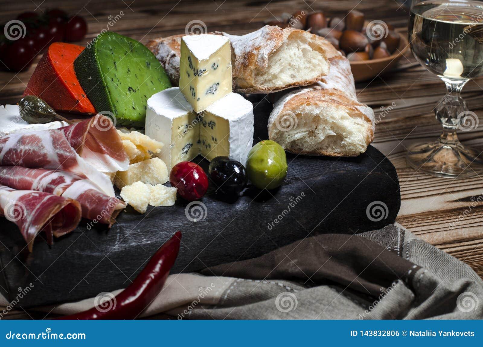 Formaggio della miscela su fondo scuro sul bordo di legno con l uva, il miele, i dadi, i pomodori ed il basilico Vista superiore