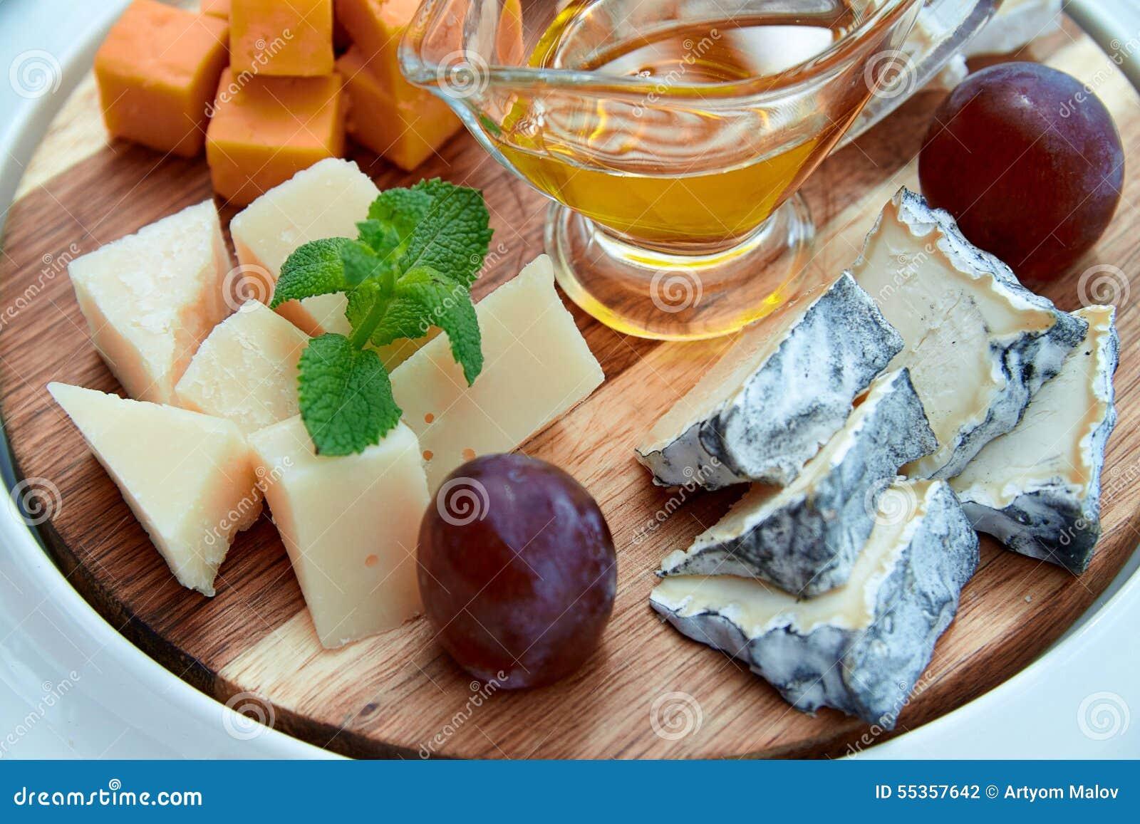 Formaggio e frutti sul piatto di legno
