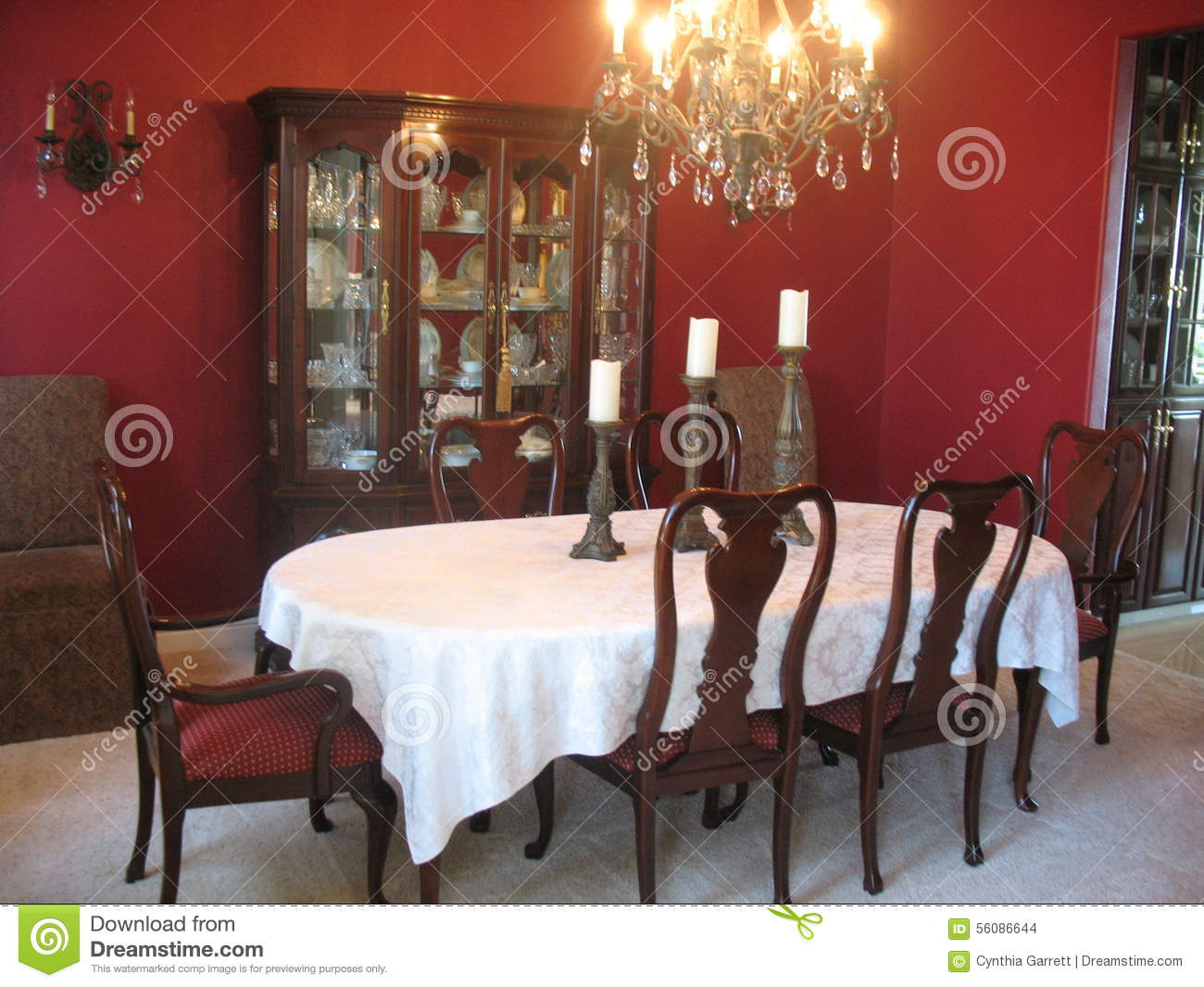 formal dining room with china cabinet and chandelier linen tablecloth