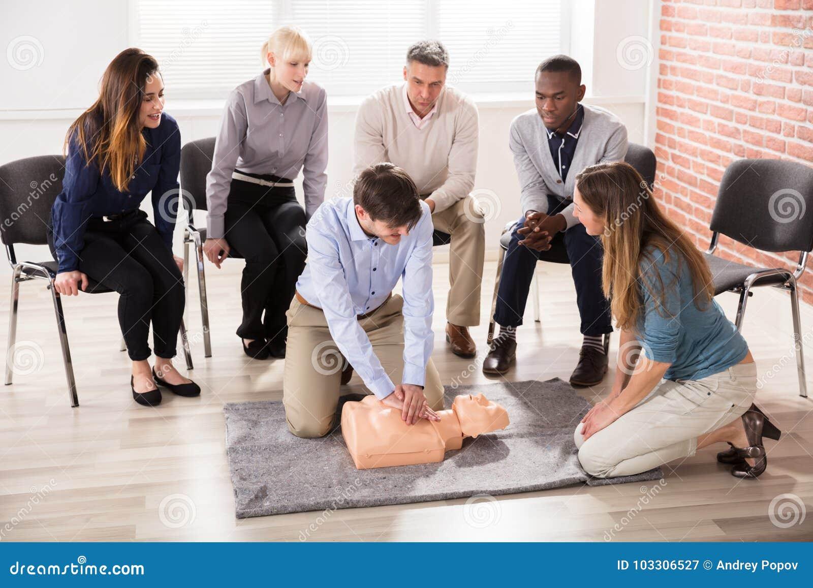Formation de CPR de Showing d instructeur de premiers secours sur le simulacre