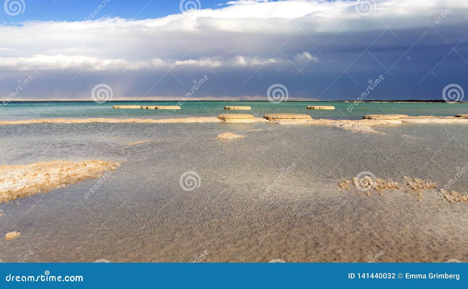 Formations de sel en mer morte des eaux de bleu et de turquoise contre le contexte d un ciel orageux en nuages