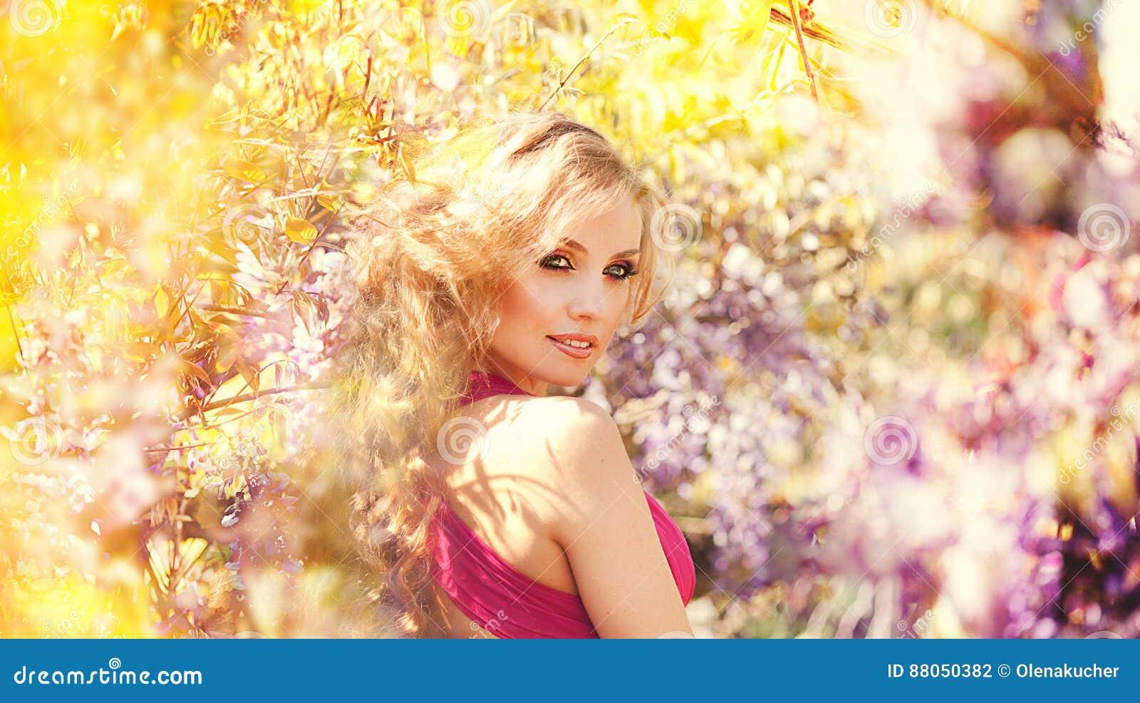 Forme el retrato de la muchacha hermosa joven que presenta contra arbustos de lila en flor