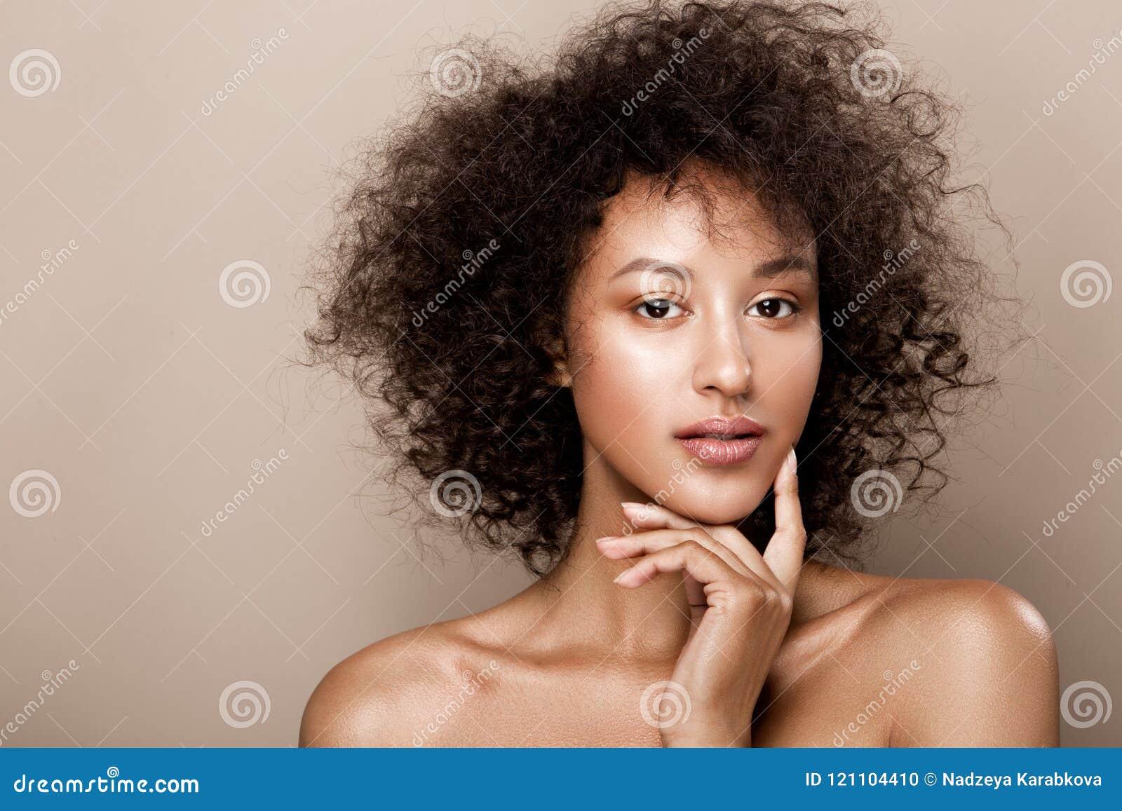 Forme el retrato del estudio de la mujer afroamericana hermosa con la piel lisa perfecta del mulato que brilla intensamente, comp