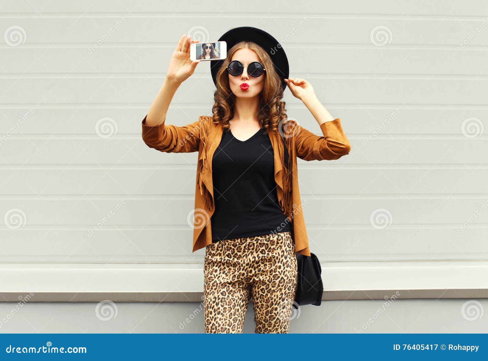 Forme a jovem mulher bonita o autorretrato de tomada modelo da imagem da foto no smartphone que veste o chapéu elegante retro, óc