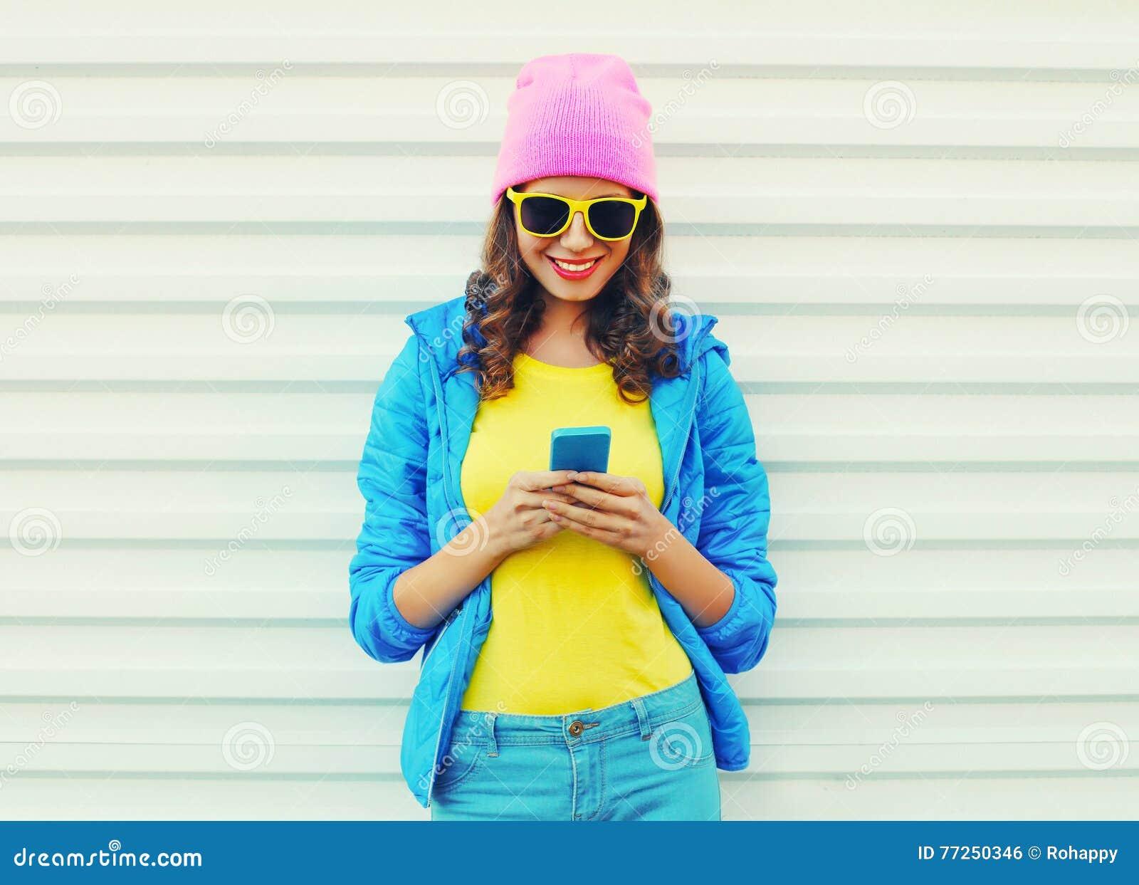 Forme a la muchacha sonriente fresca feliz que usa smartphone en ropa colorida sobre el fondo blanco que lleva las gafas de sol r