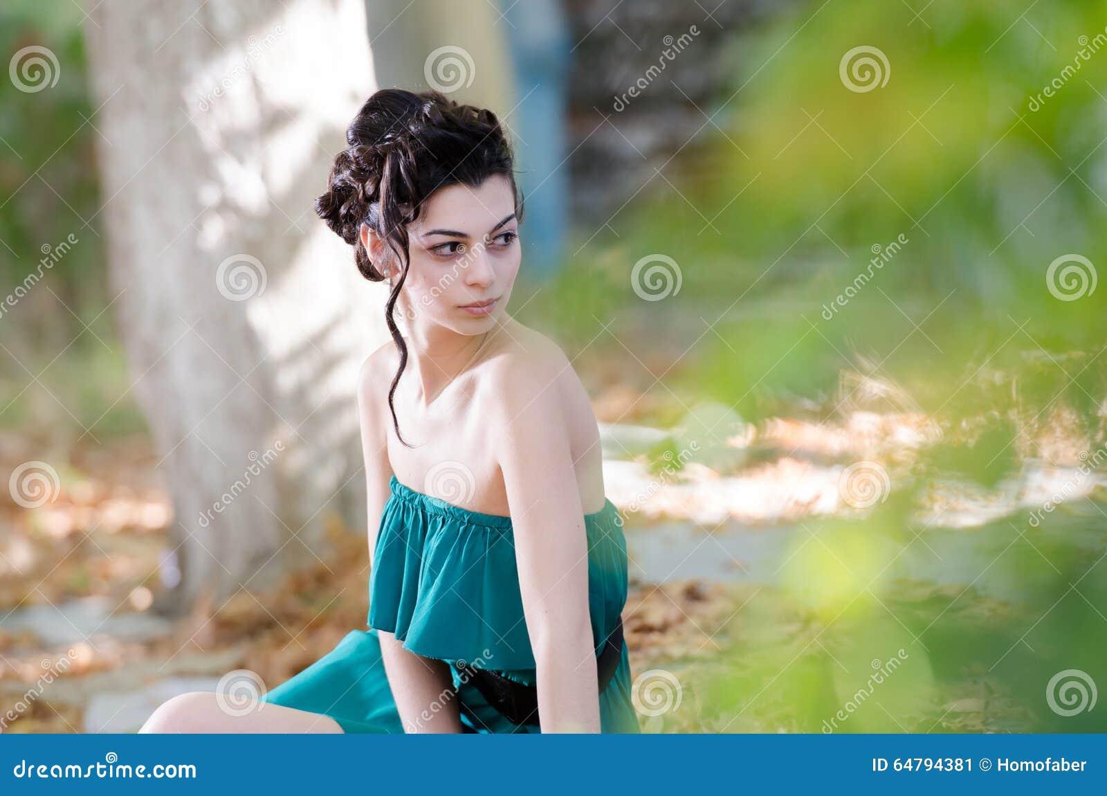 Forme a la mujer delgada que lleva la acera que se sienta del vestido corto sin tirantes verde