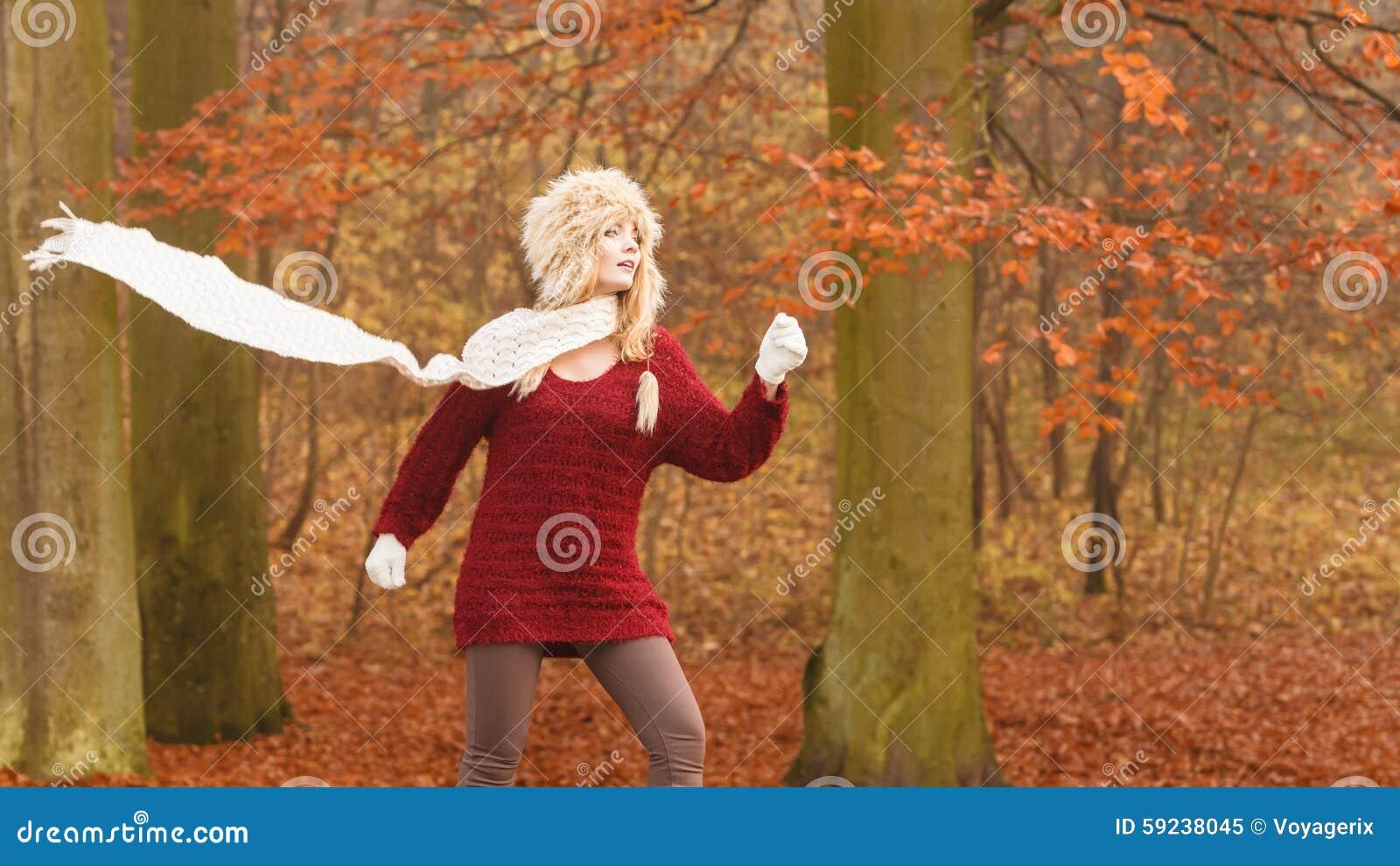 Forme a la mujer en bosque ventoso del parque del otoño de la caída