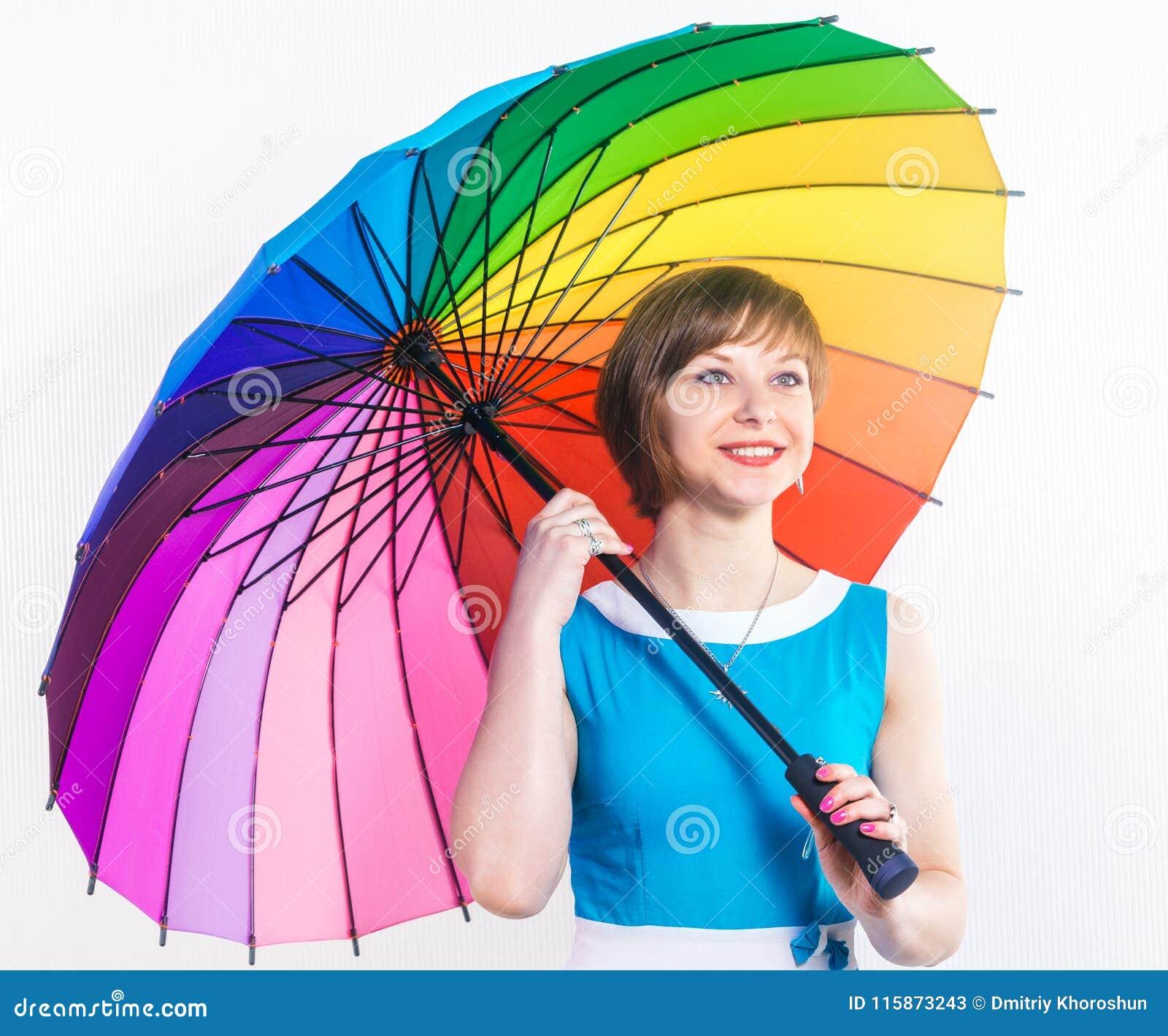 Forme a la mujer joven bastante sonriente que sostiene el paraguas colorido del arco iris que lleva un vestido azul sobre el fond