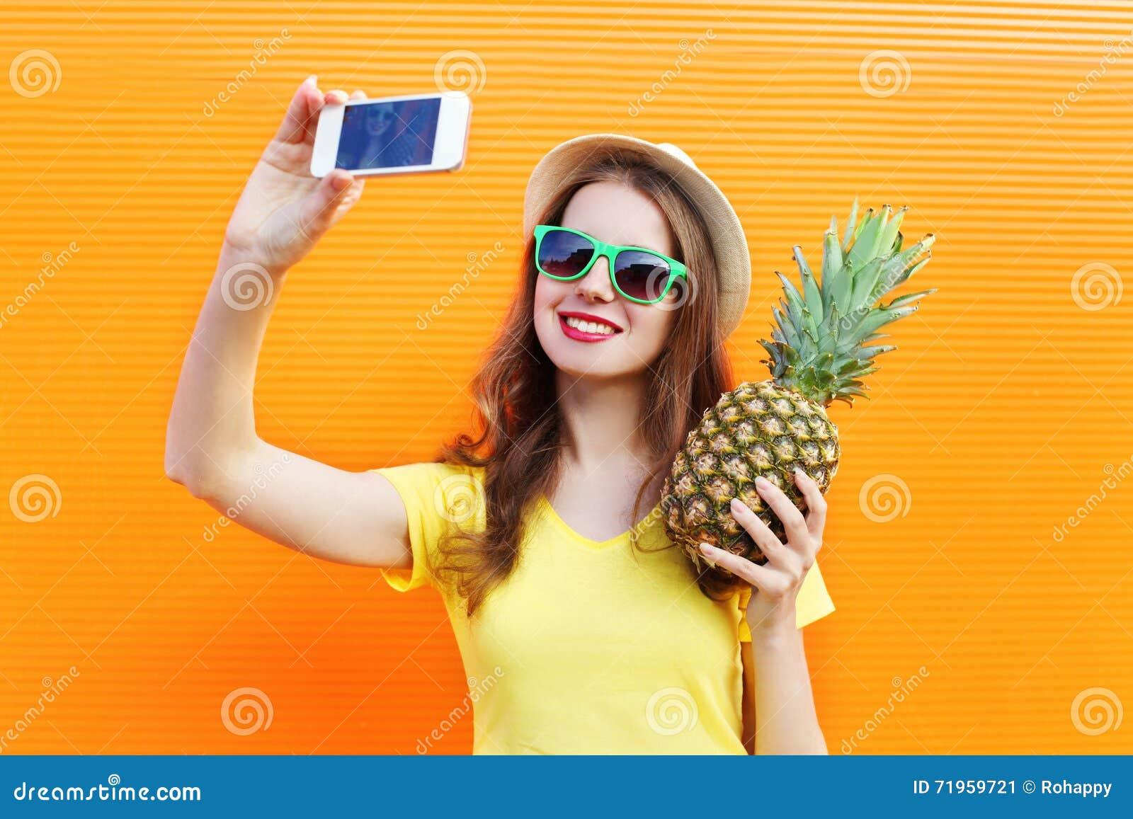 Forme a menina consideravelmente fresca nos óculos de sol, chapéu com o abacaxi que toma o selfie da imagem no smartphone sobre c