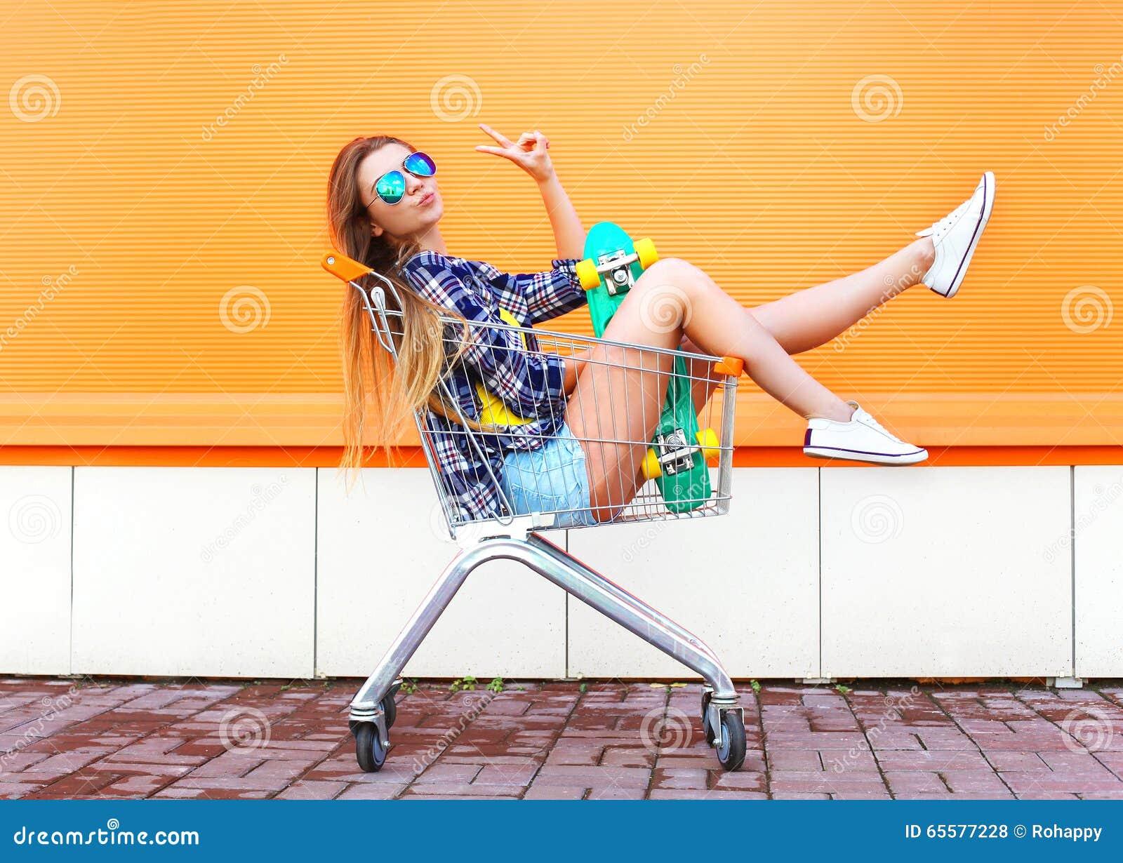 Forme a menina fresca que tem o divertimento no carro do trole da compra com skate
