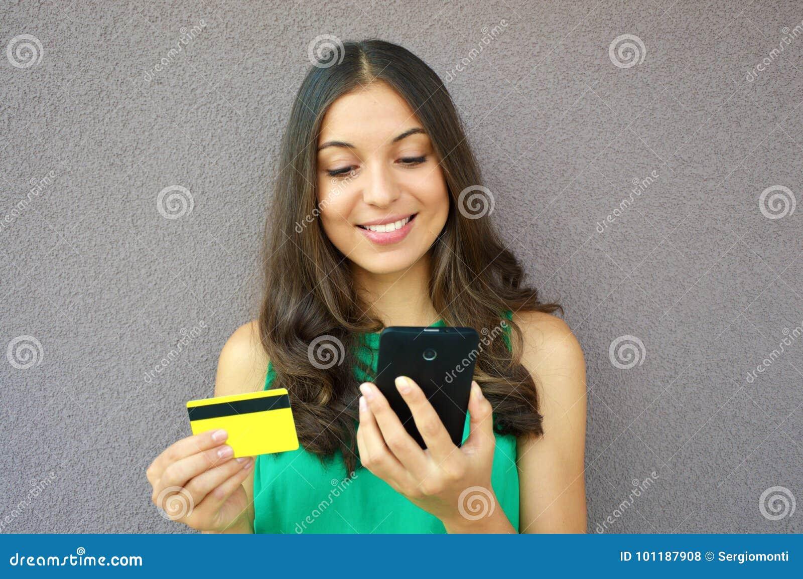 Forme a menina que compra em linha com o cartão esperto do telefone e de crédito isolado no fundo violeta