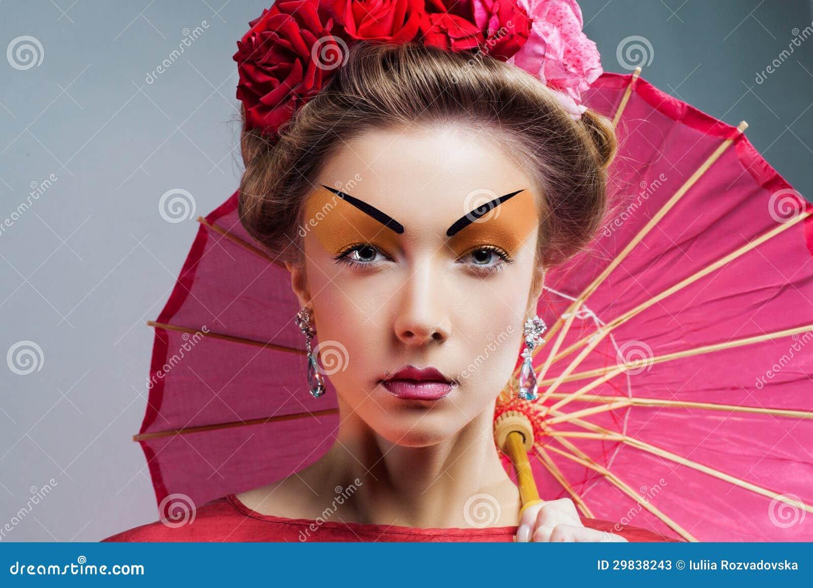 Forme a mulher asiática que veste o quimono vermelho japonês tradicional