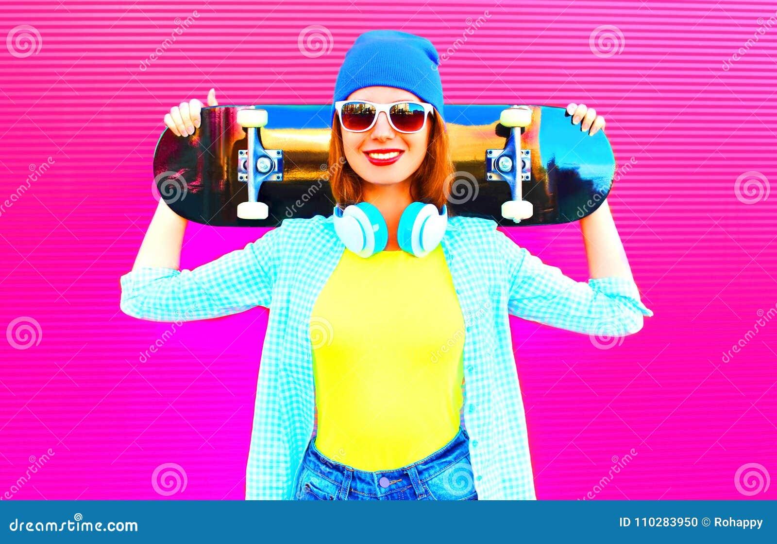 Forme a mulher consideravelmente de sorriso com um skate na cidade no rosa