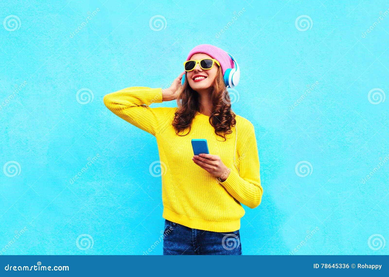 Forme a mulher despreocupada consideravelmente doce que escuta a música nos fones de ouvido com o smartphone que veste óculos de