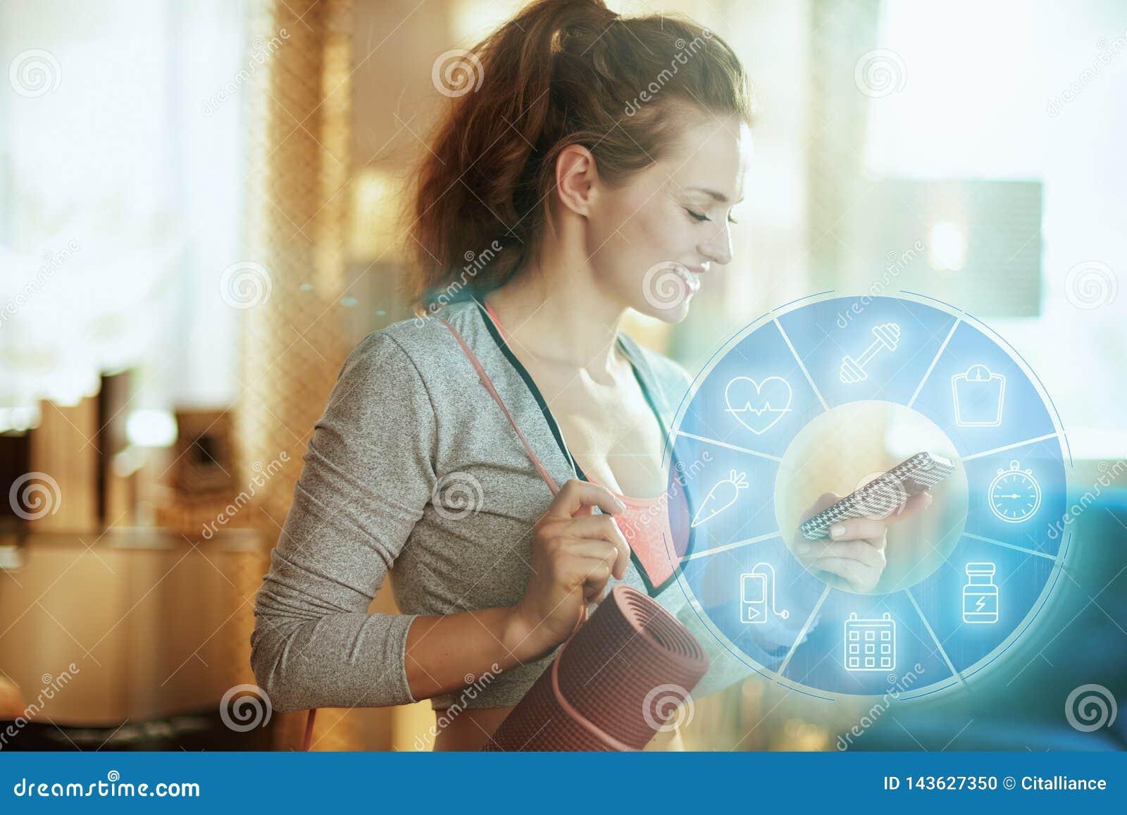 Forme physique de femme de sports donnant des leçons particulières sur l Internet utilisant le smartphone