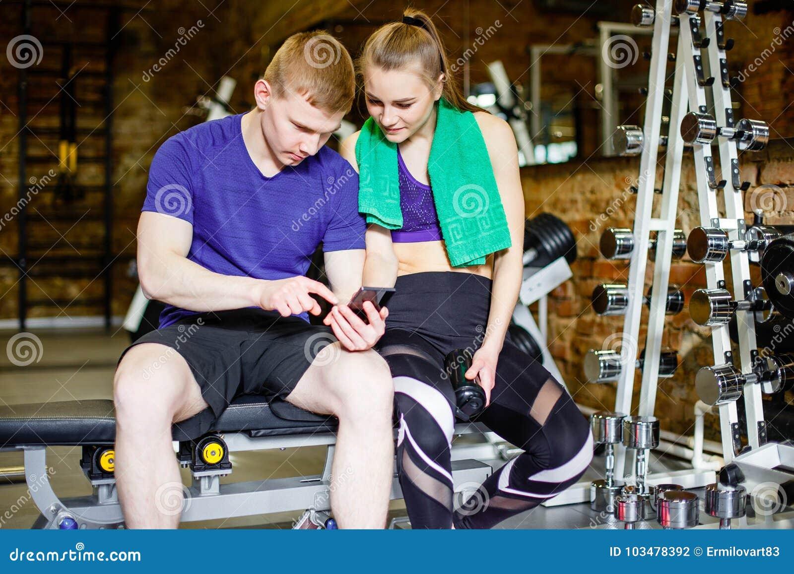 Forme physique, sport, technologie et concept de régime - femme et entraîneur personnel avec le smartphone et les bouteilles d ea