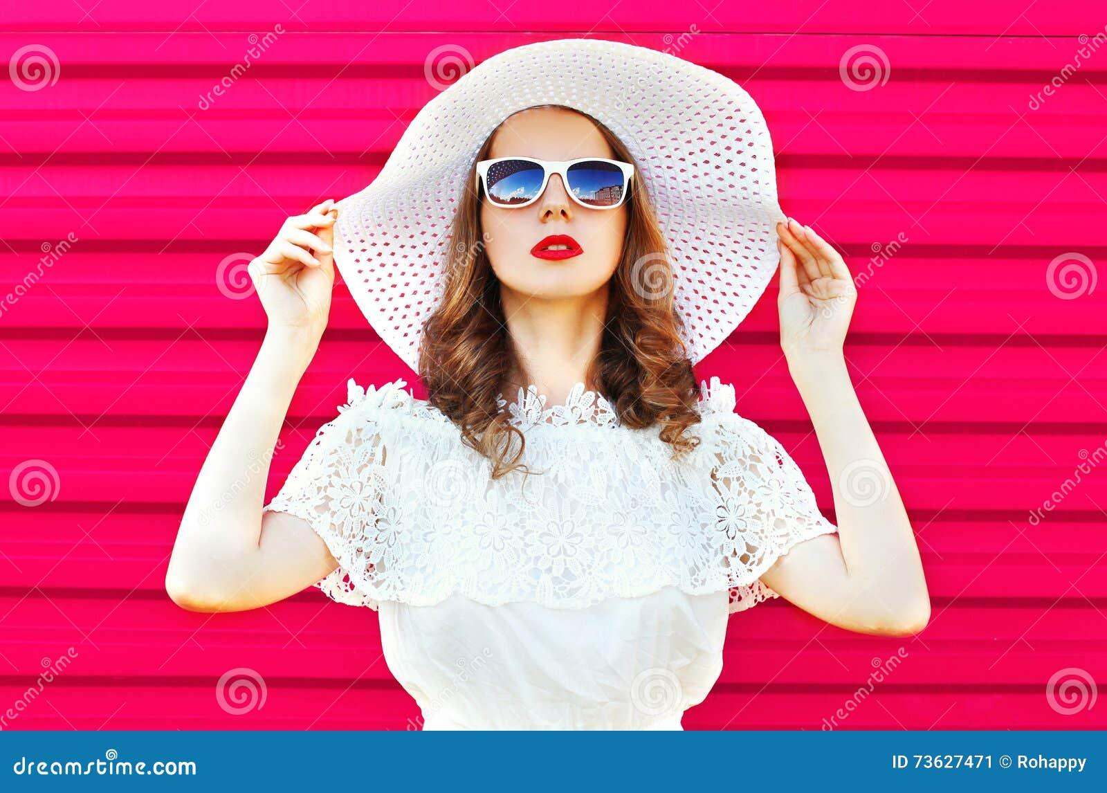 Forme a retrato la mujer bonita en el sombrero de paja blanco del verano sobre rosa colorido