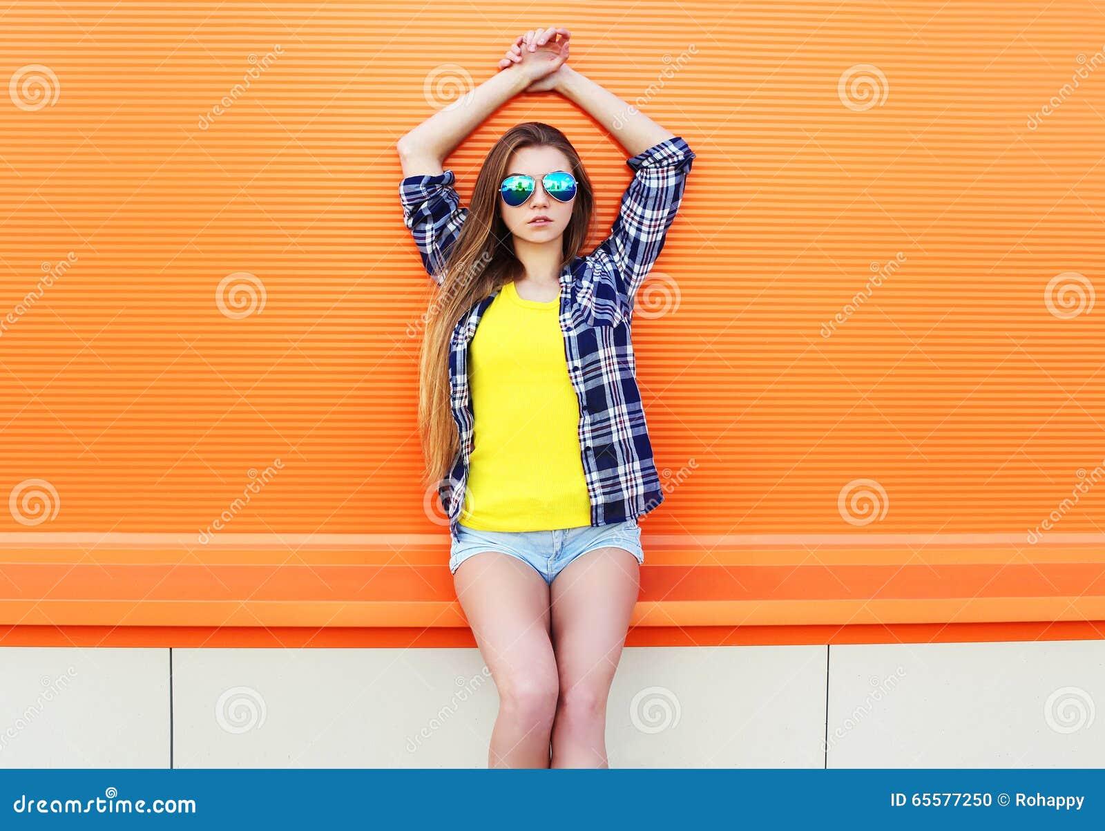 Forme a vestir bonito da menina óculos de sol e short na cidade sobre colorido