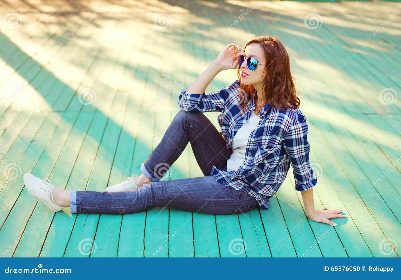 Forme a vestir bonito da mulher óculos de sol e a camisa quadriculado