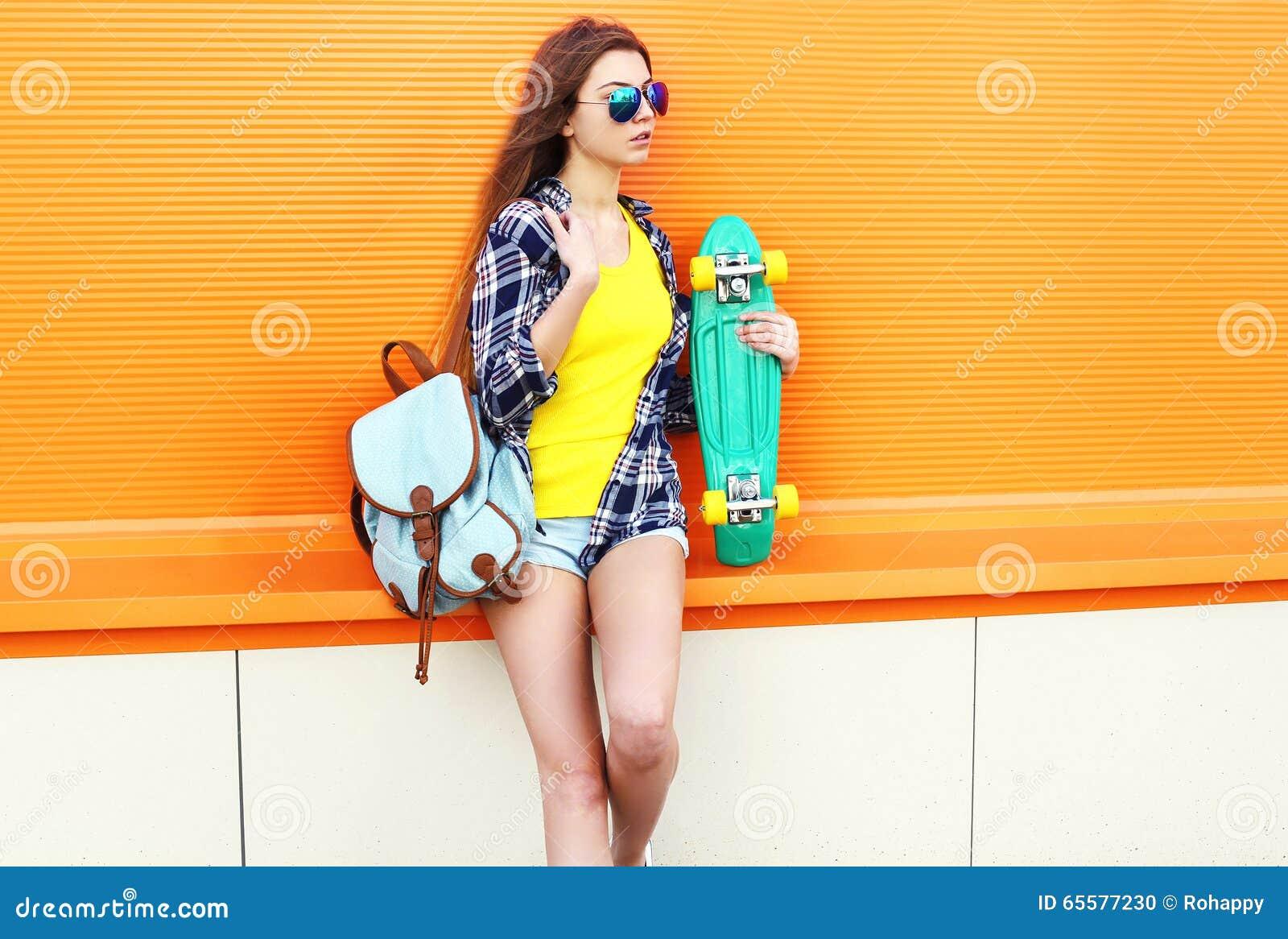 Forme a vestir consideravelmente fresco da menina óculos de sol e trouxa com o skate sobre a laranja