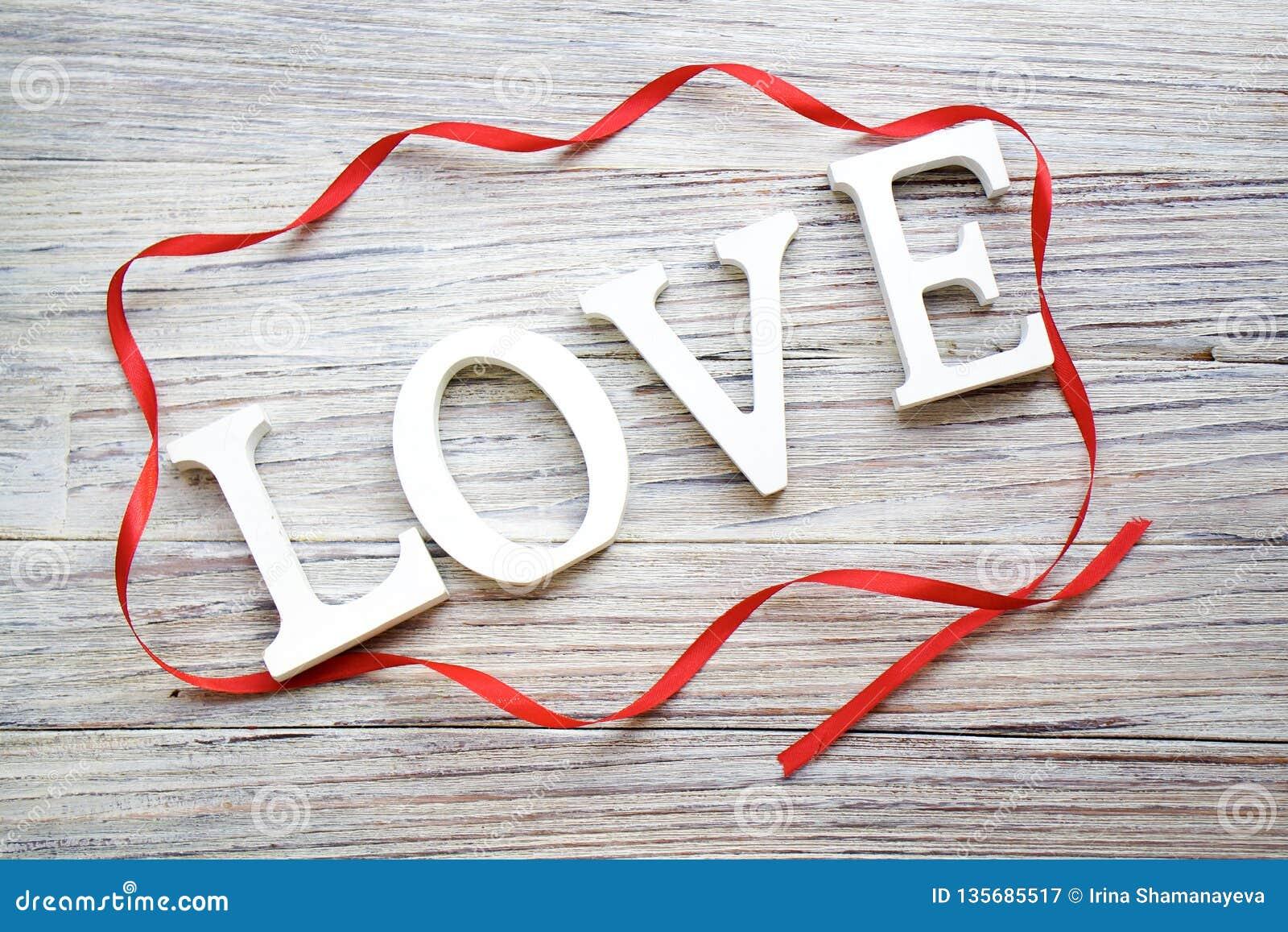 Formułuje miłości biali drewniani listy z czerwonym atłasowym faborkiem na białym drewnianym tle