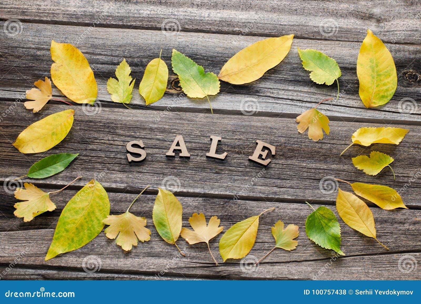 Formułuje sprzedaż na drewnianym tle, rama żółci liście