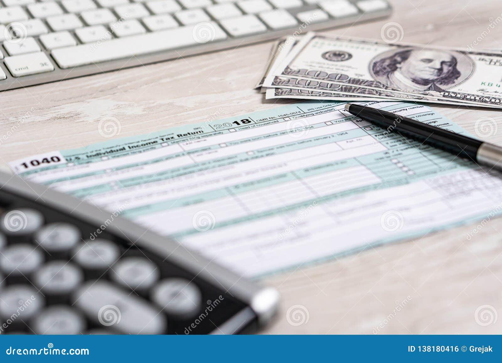 Formulário de imposto 1040 dos E.U. com pena, calculadora e notas de dólar conceito branco do negócio do documento EUA da lei do