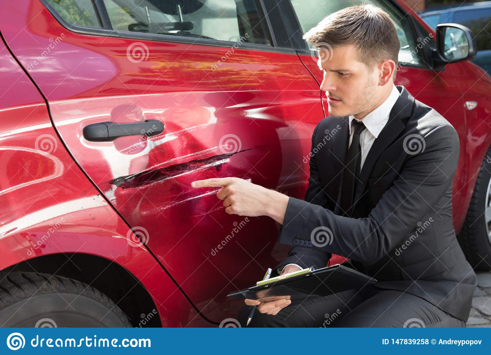 Formulario de relleno del seguro del hombre cerca del coche da?ado