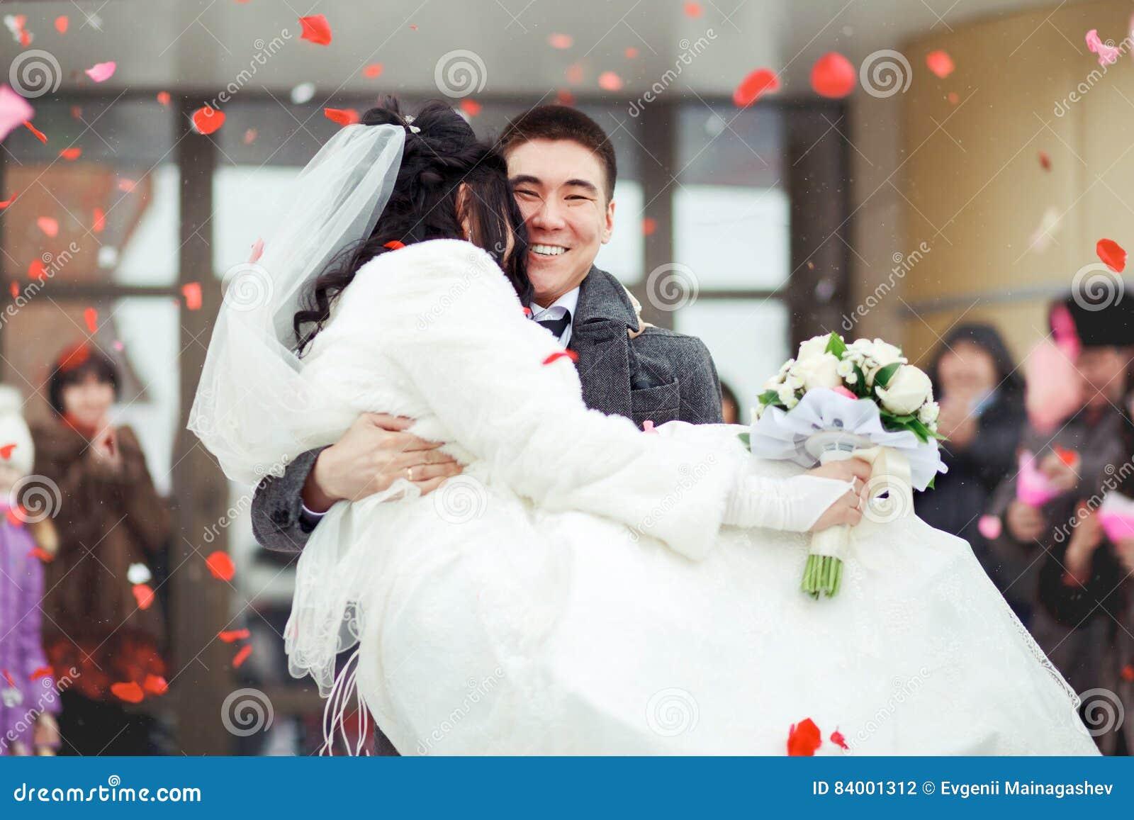 Fornala przewożenia panna młoda w jego rękach tłum rzuca płatki i ryż szczęśliwy ślub