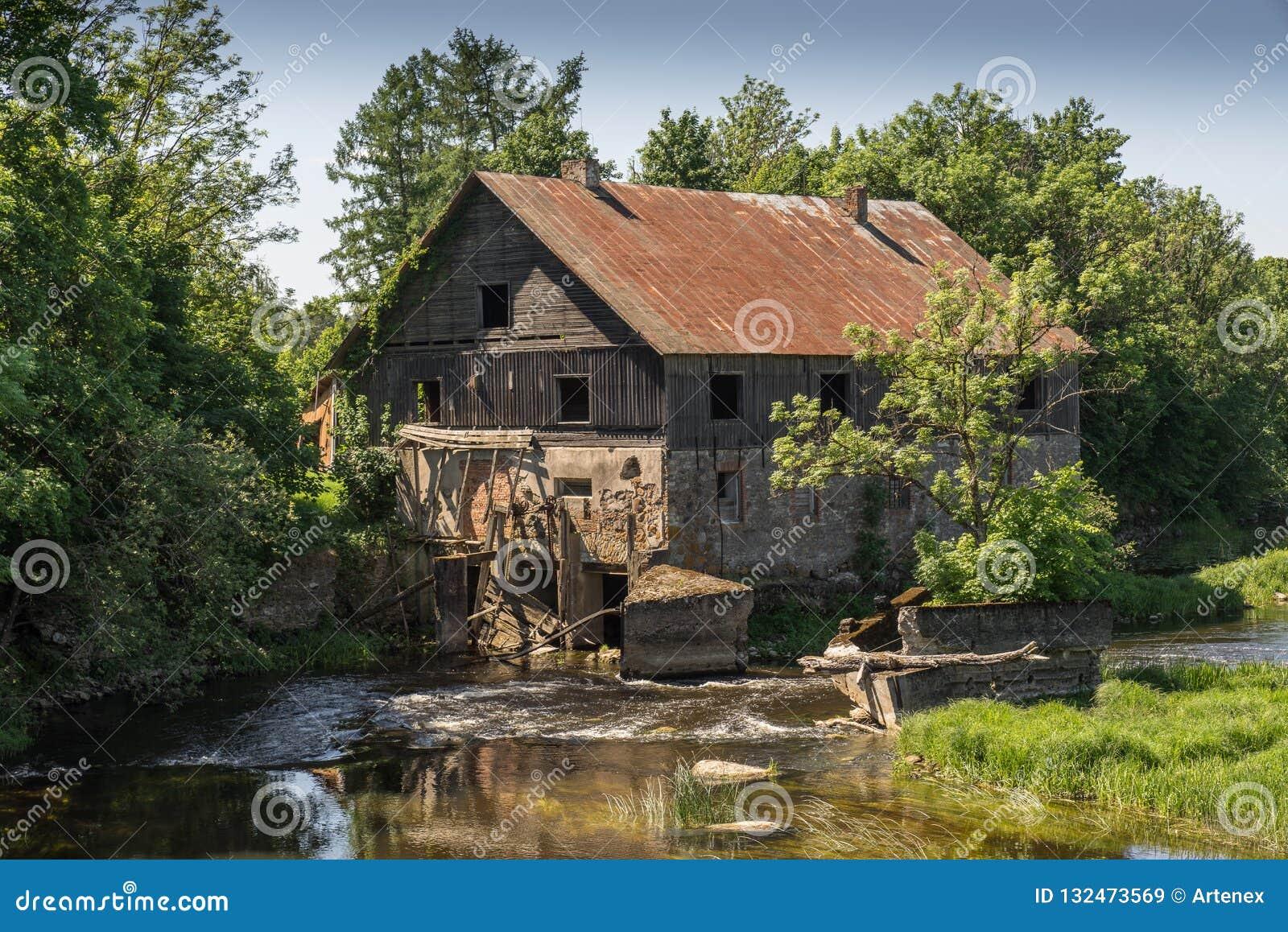 Forntida övergett vatten maler omgivet av den härliga naturen Hus som byggs av stenen och trä, yttre väggar och förfallen bro