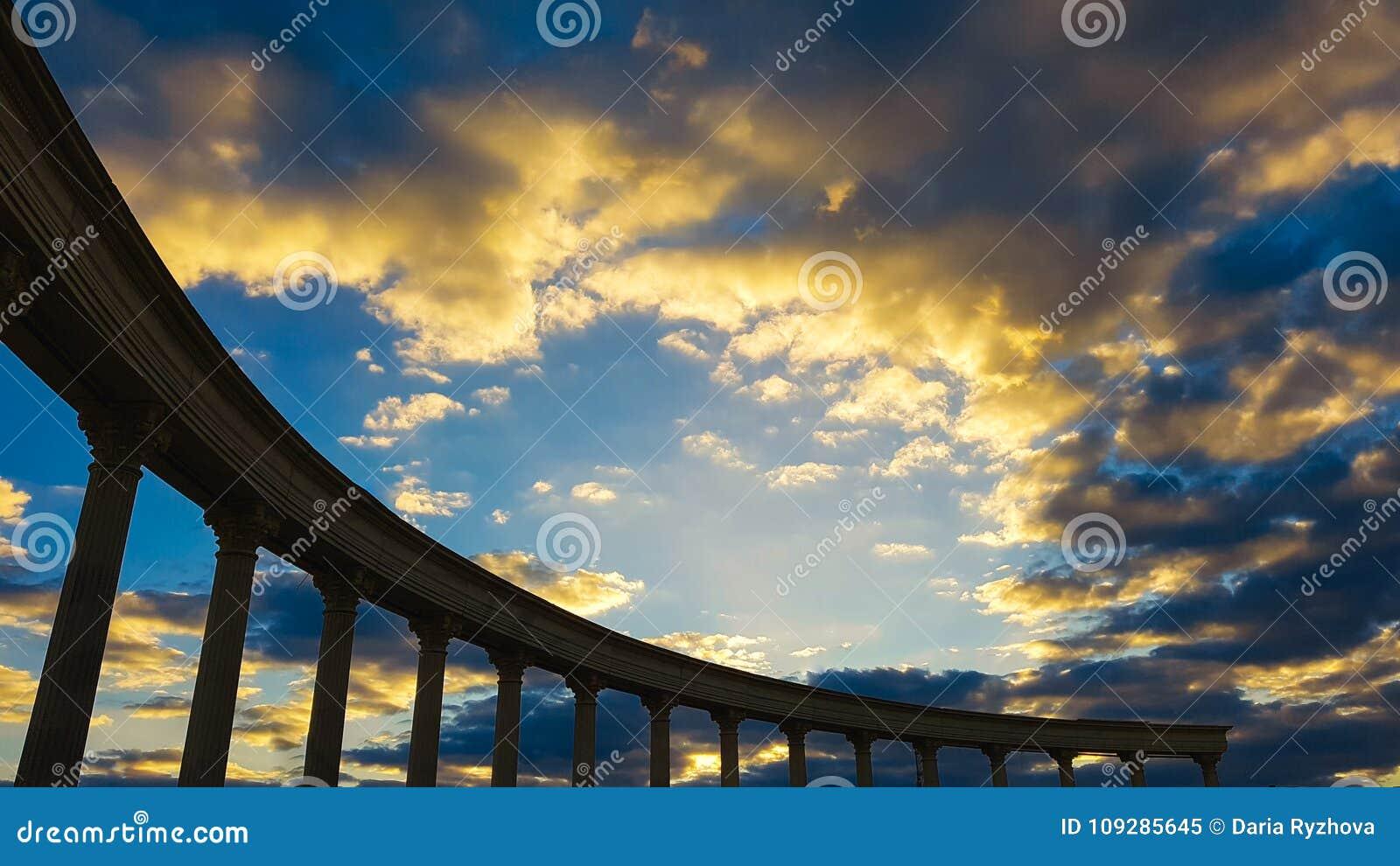 Forntida kolonnkontur på himmel för inställningssol
