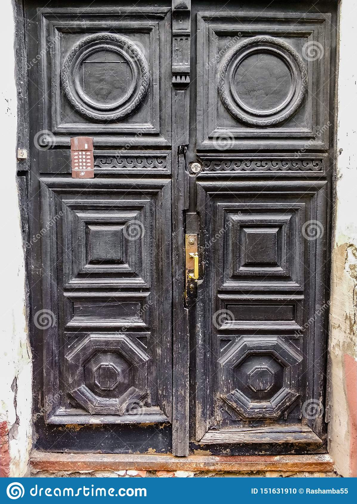 Forntida träsvarta dörrar med infill- och dörrhandtaget