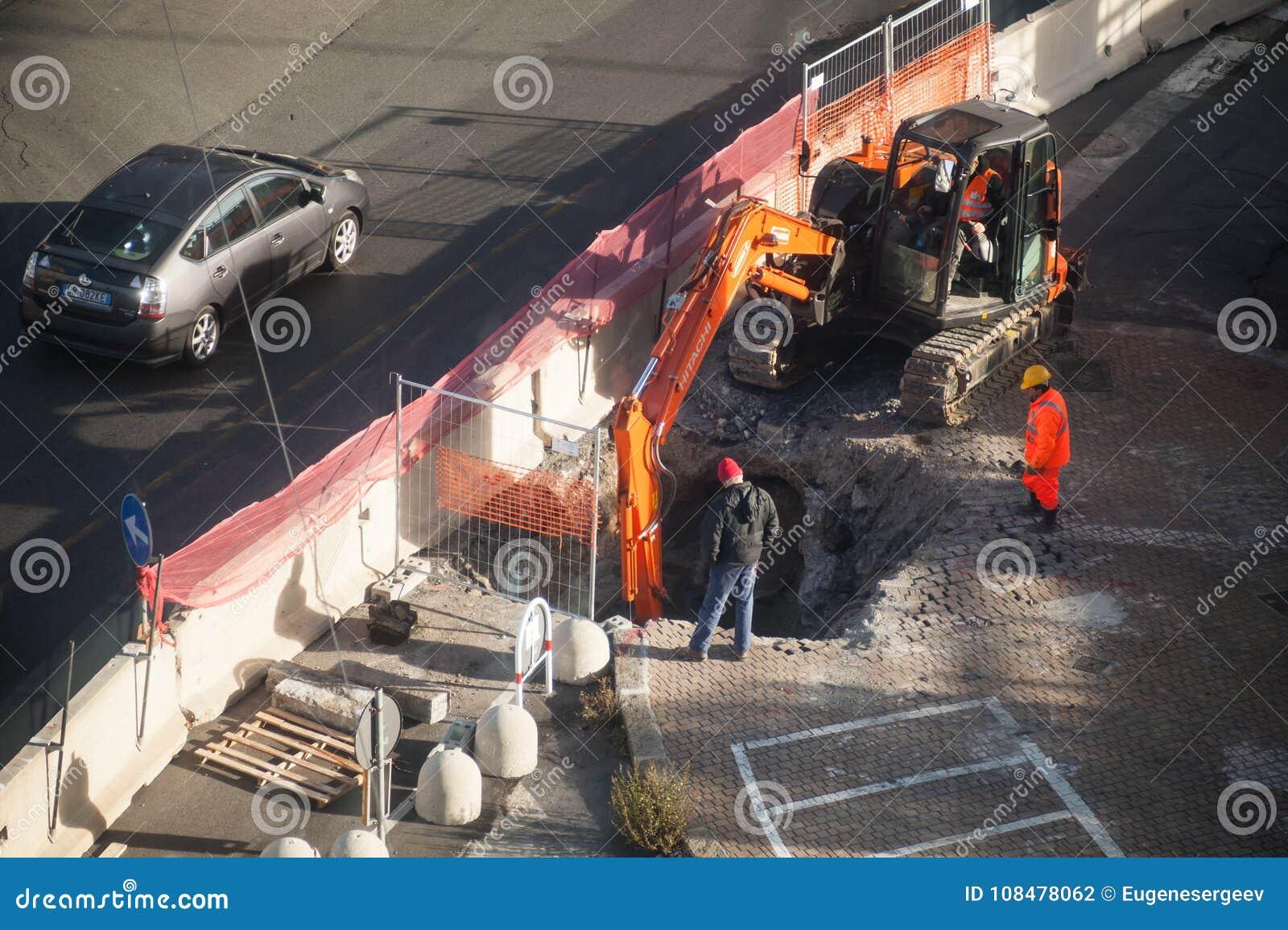 Foro di vangata dei lavoratori in asfalto con l escavatore