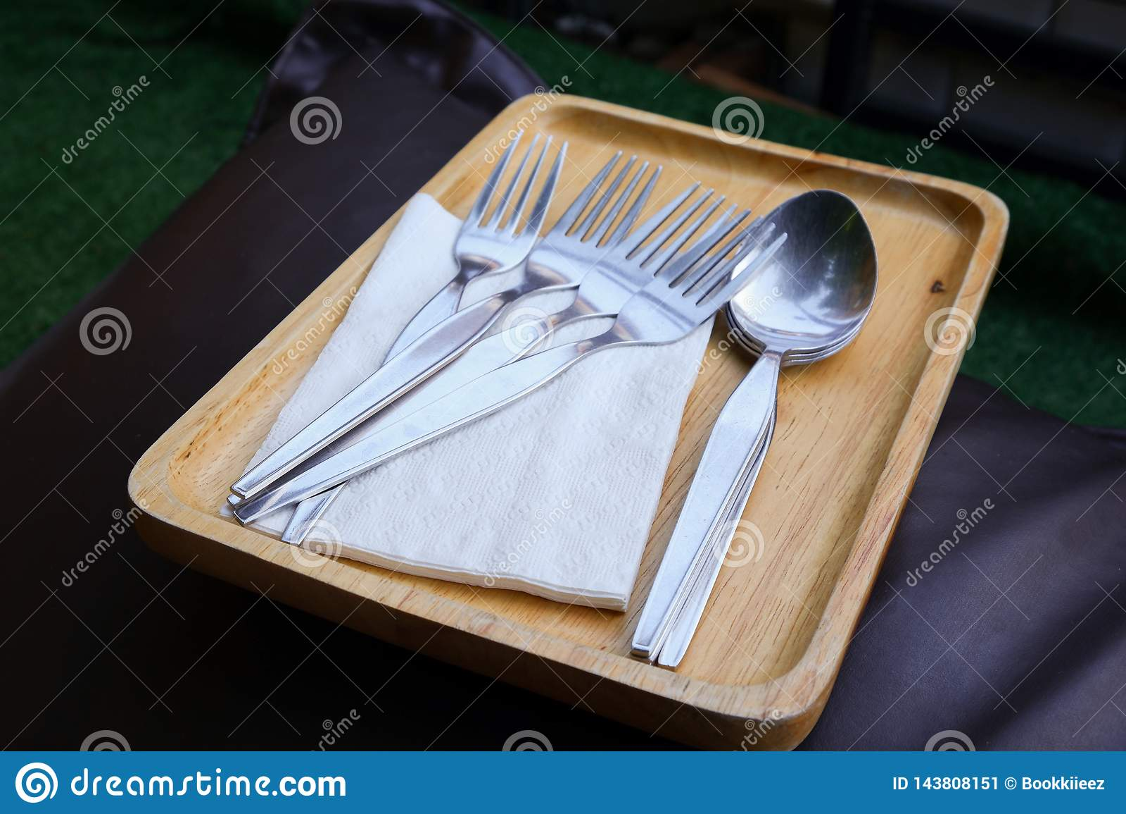 Forquilhas, colheres, e lenços de papel na bandeja de madeira