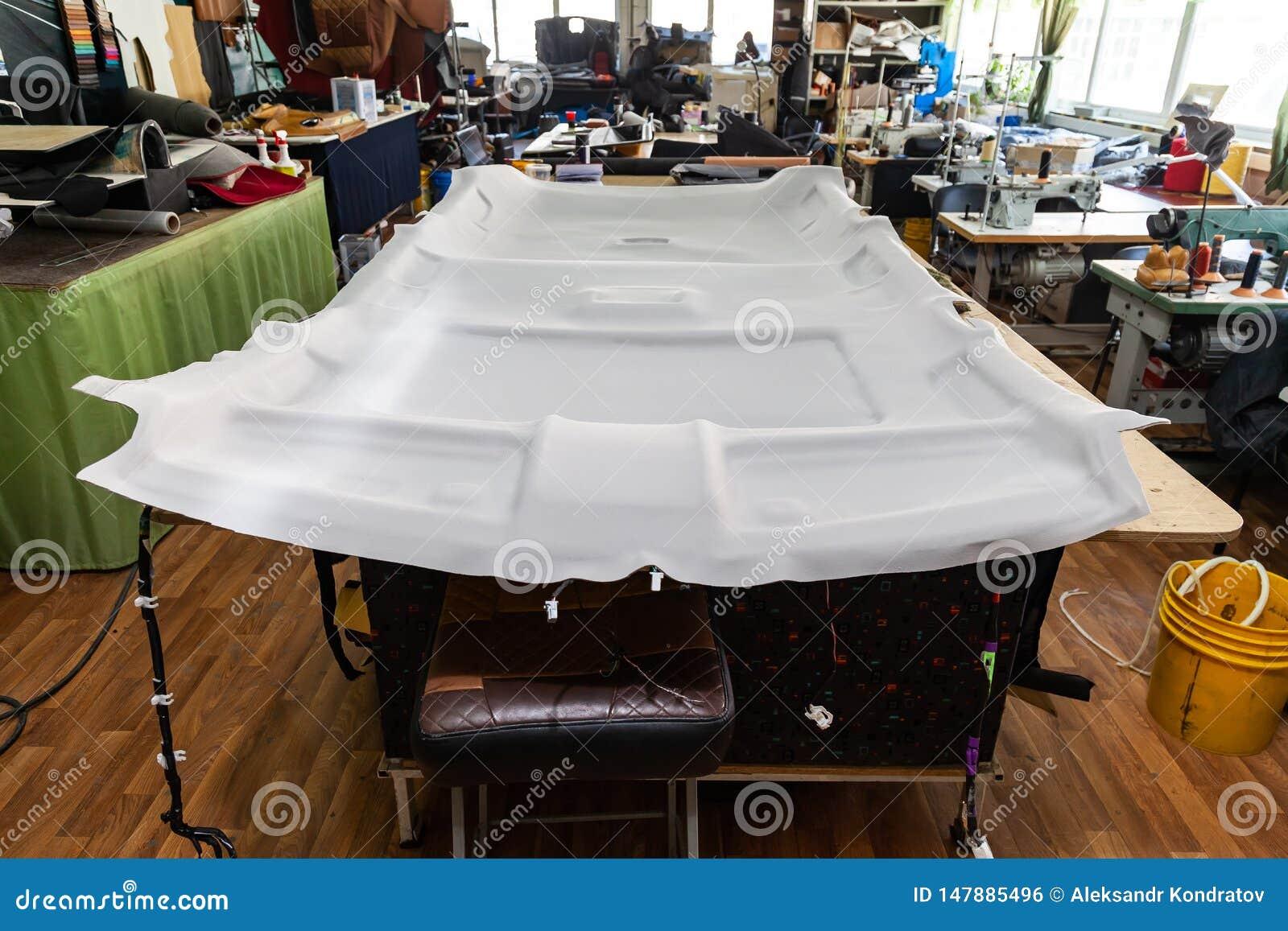 Forro de teto cinzento removido do carro para ajustar e apoiar com o material macio cinzento em uma tabela na oficina no