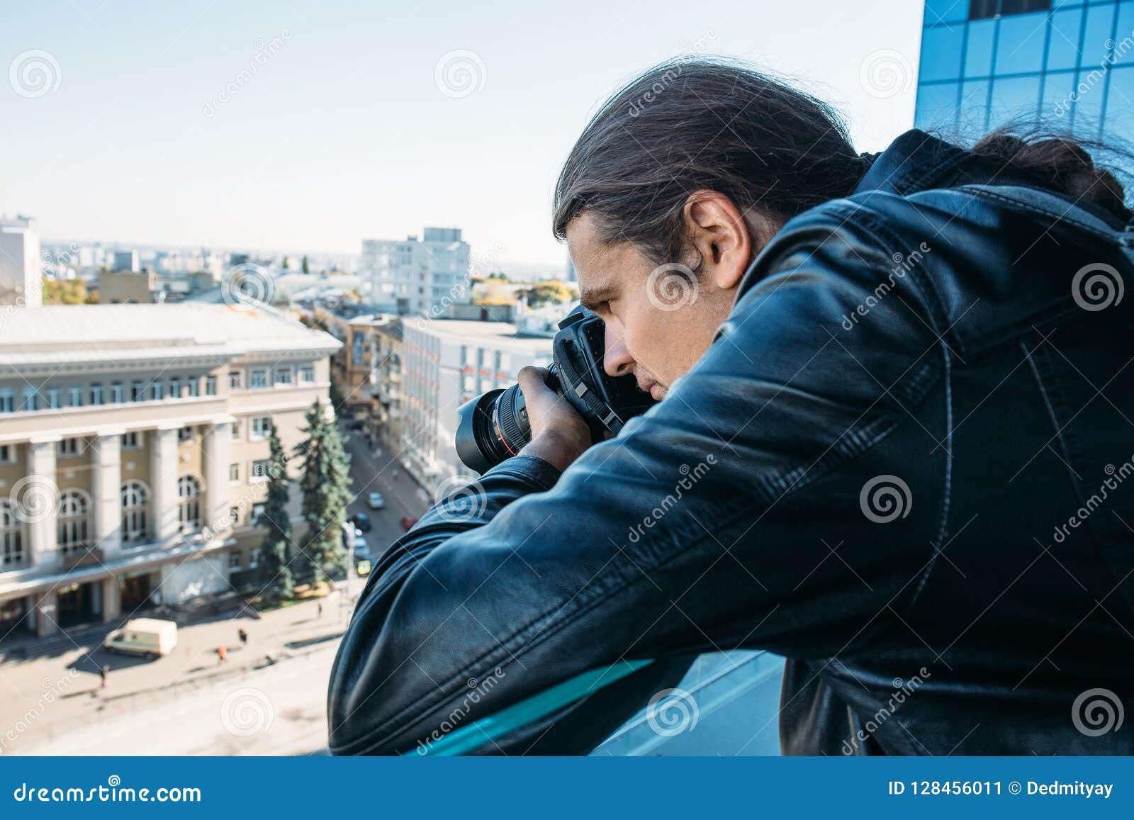 Forscher oder privater Detektiv oder Reporter oder Paparazzi, die Foto vom Balkon des Gebäudes mit Berufskamera machen