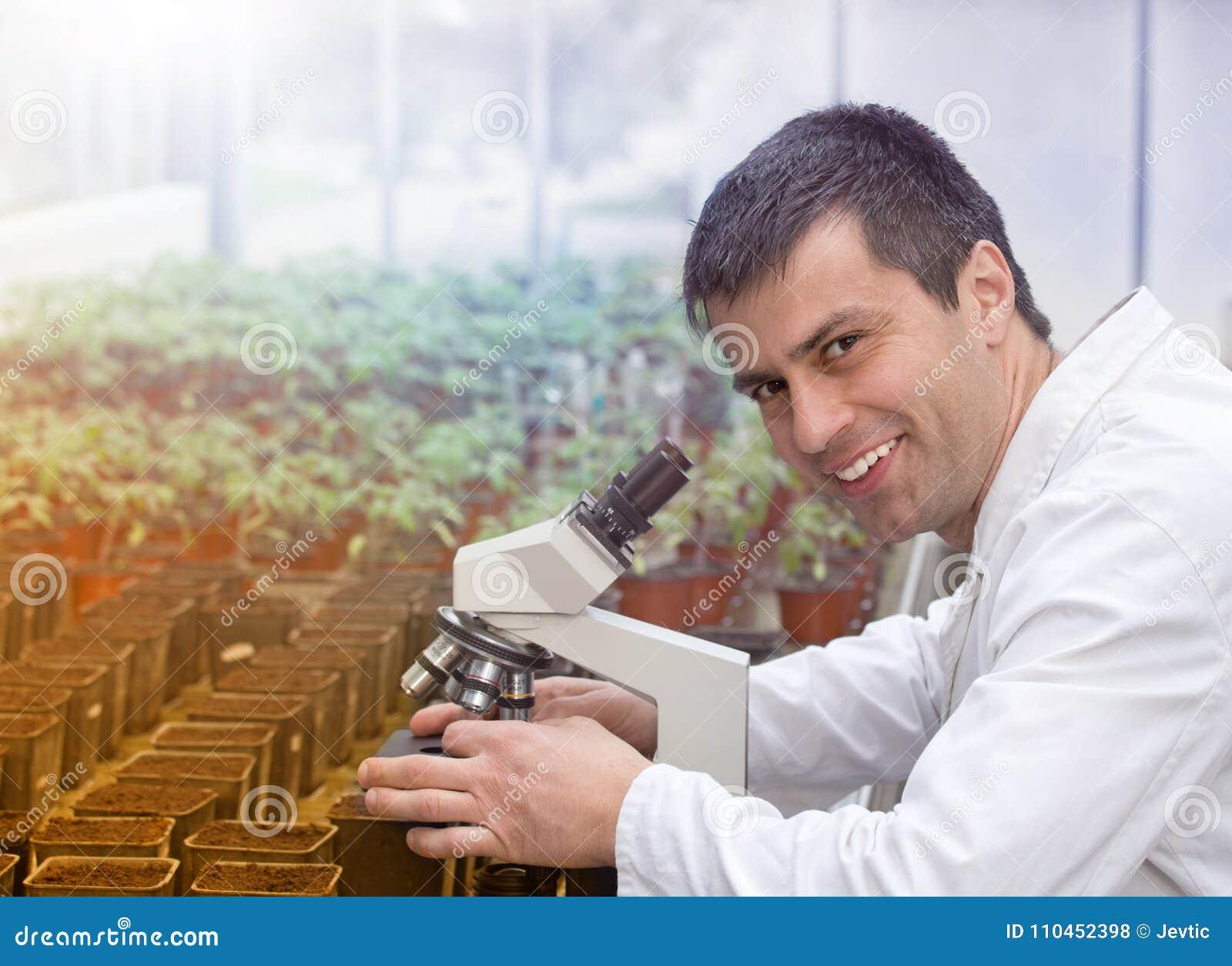 Forskare med mikroskopet i grönt hus