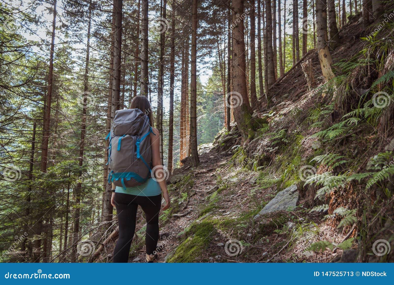 Forte donna che fa un escursione nelle montagne