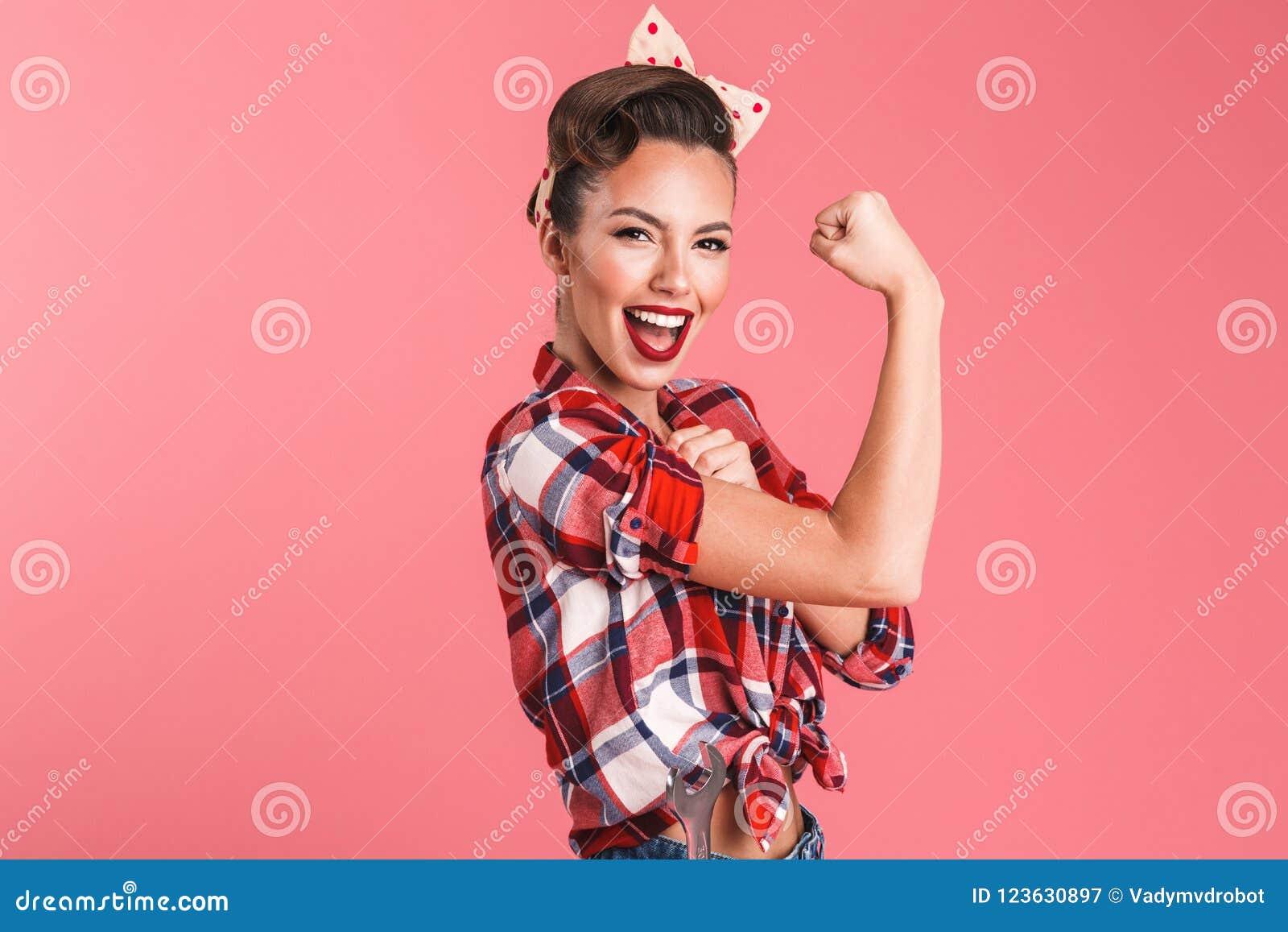 Forte giovane donna splendida di pin-up che mostra il bicipite