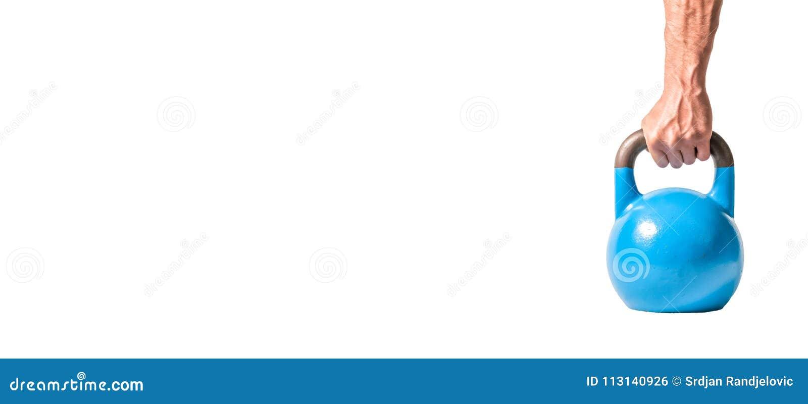 Forte mano muscolare dell uomo con i muscoli che giudicano kettlebell pesante blu parzialmente isolato su fondo bianco