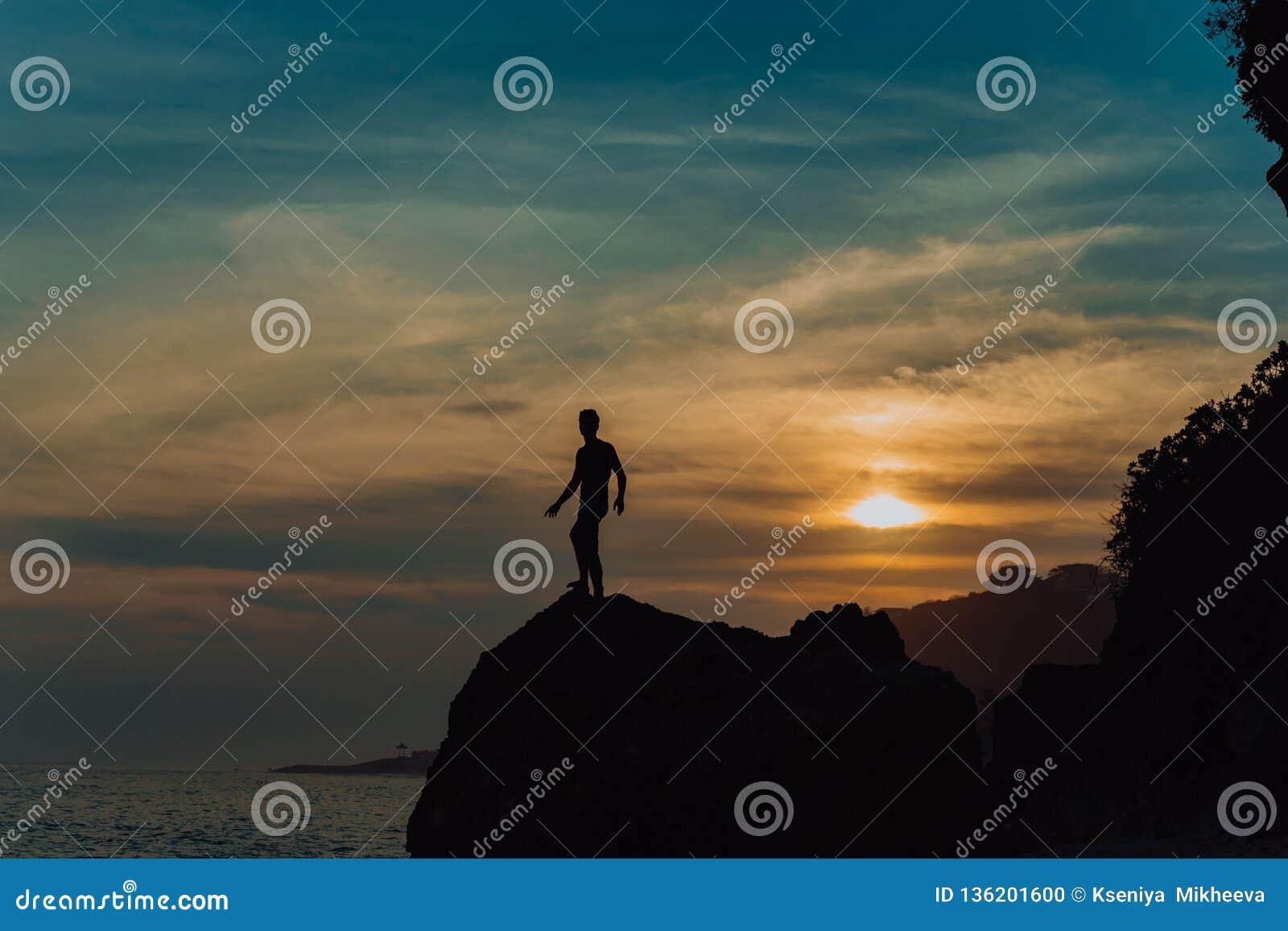 Forte uomo di yoga di forma fisica sulla spiaggia della roccia vicino all oceano Concetto, pace e successo armonici Siluetta