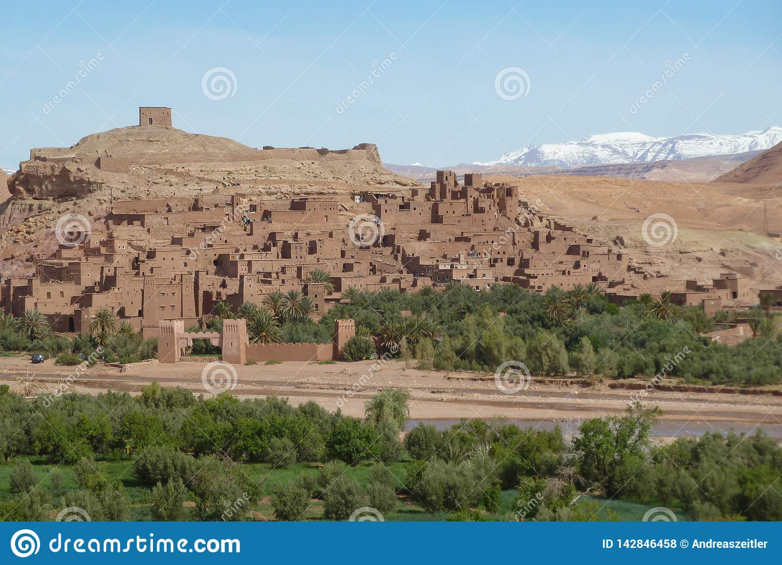 Fortified city of Ait Benhaddou along the former caravan route between the Sahara and Marrakech in Morocco with snow covered Atlas